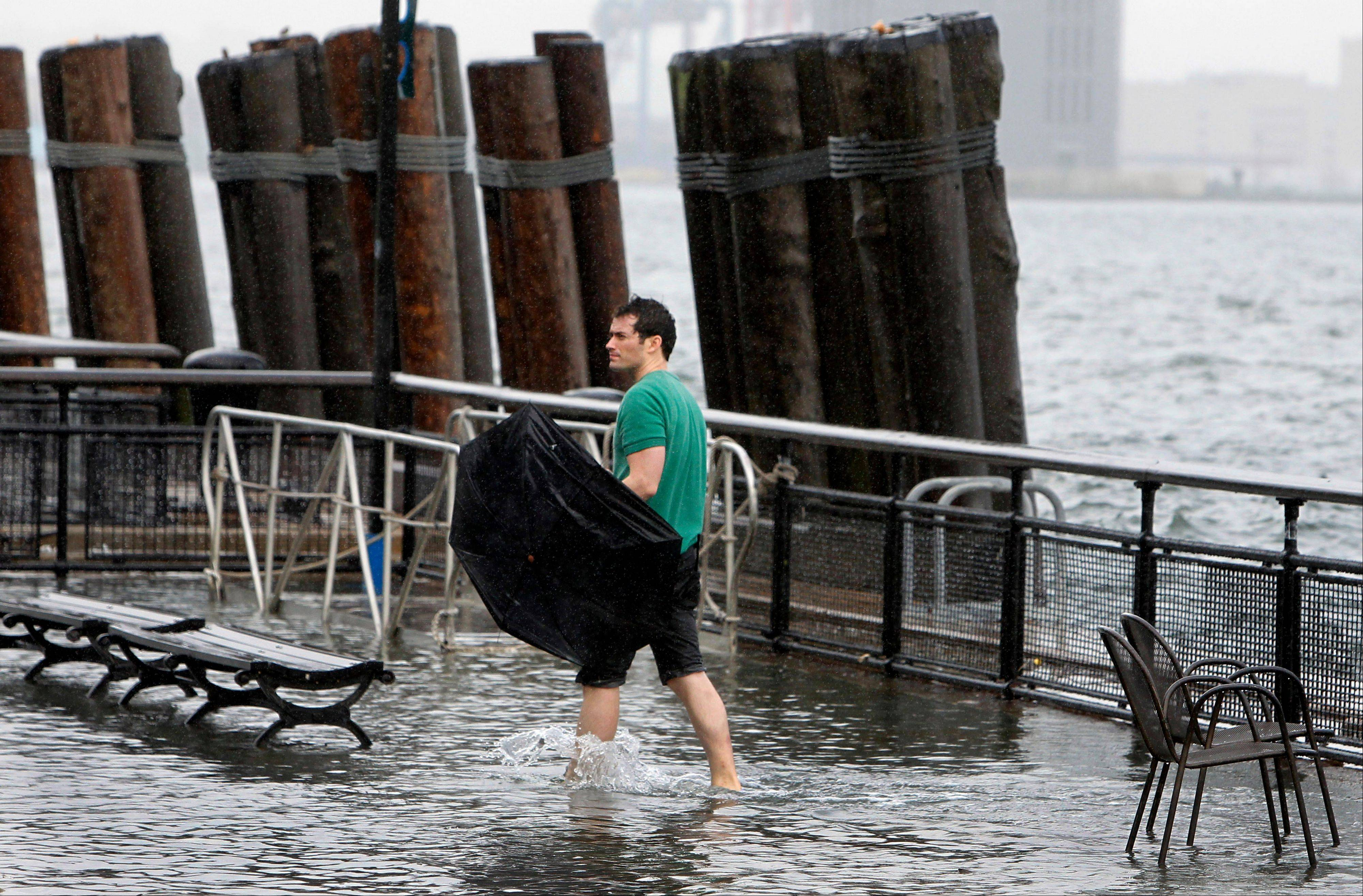 A man walks through flood water along the seawall in Battery Park as Tropical Storm Irene passes through New York, Sunday, August 28, 2011. Seawater surged into the streets of Manhattan on Sunday as Tropical Storm Irene slammed into New York, downgraded from a hurricane but still unleashing furious wind and rain. The flooding threatened Wall Street and the heart of the global financial network.