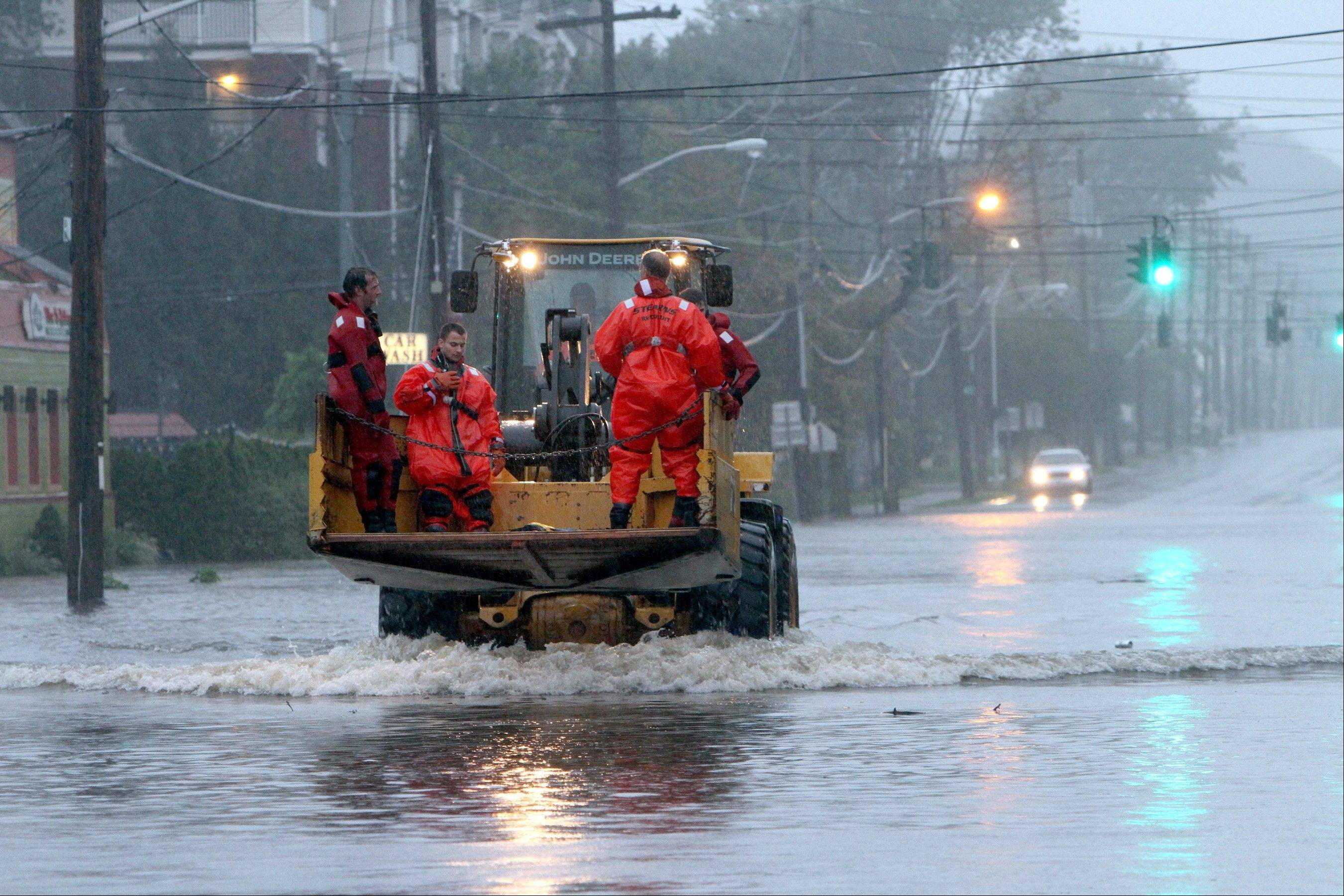 Village of Mamaroneck, N.Y. rescue swimmers ride on the front of a pay-loader en-route to their next mission during Hurricane Irene in Mamaroneck during Hurricane Irene Sunday, Aug. 28, 2011.