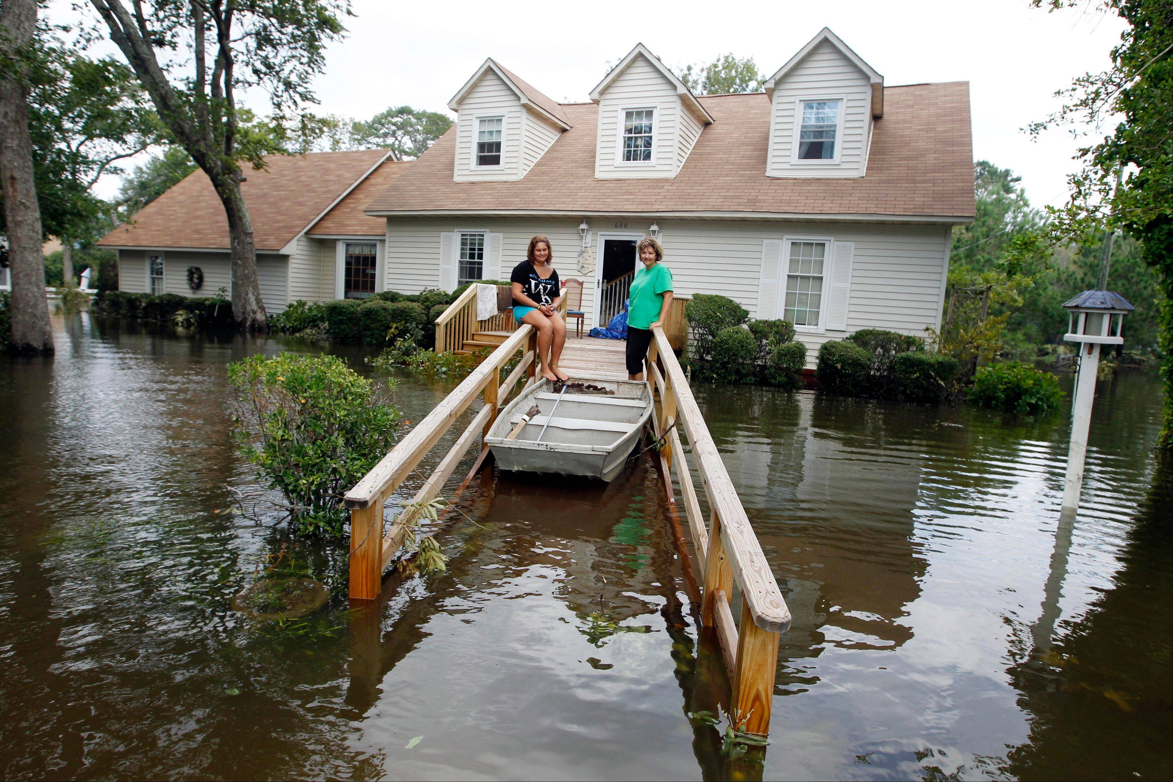 Lechelle, right, and her daughter Haleigh Spalding sit in front of their flooded home after a storm surge on the Outer Banks in Kitty Hawk, N.C., Sunday, Aug. 28, 2011 in the aftermath of Hurricane Irene after it left the North Carolina coast.