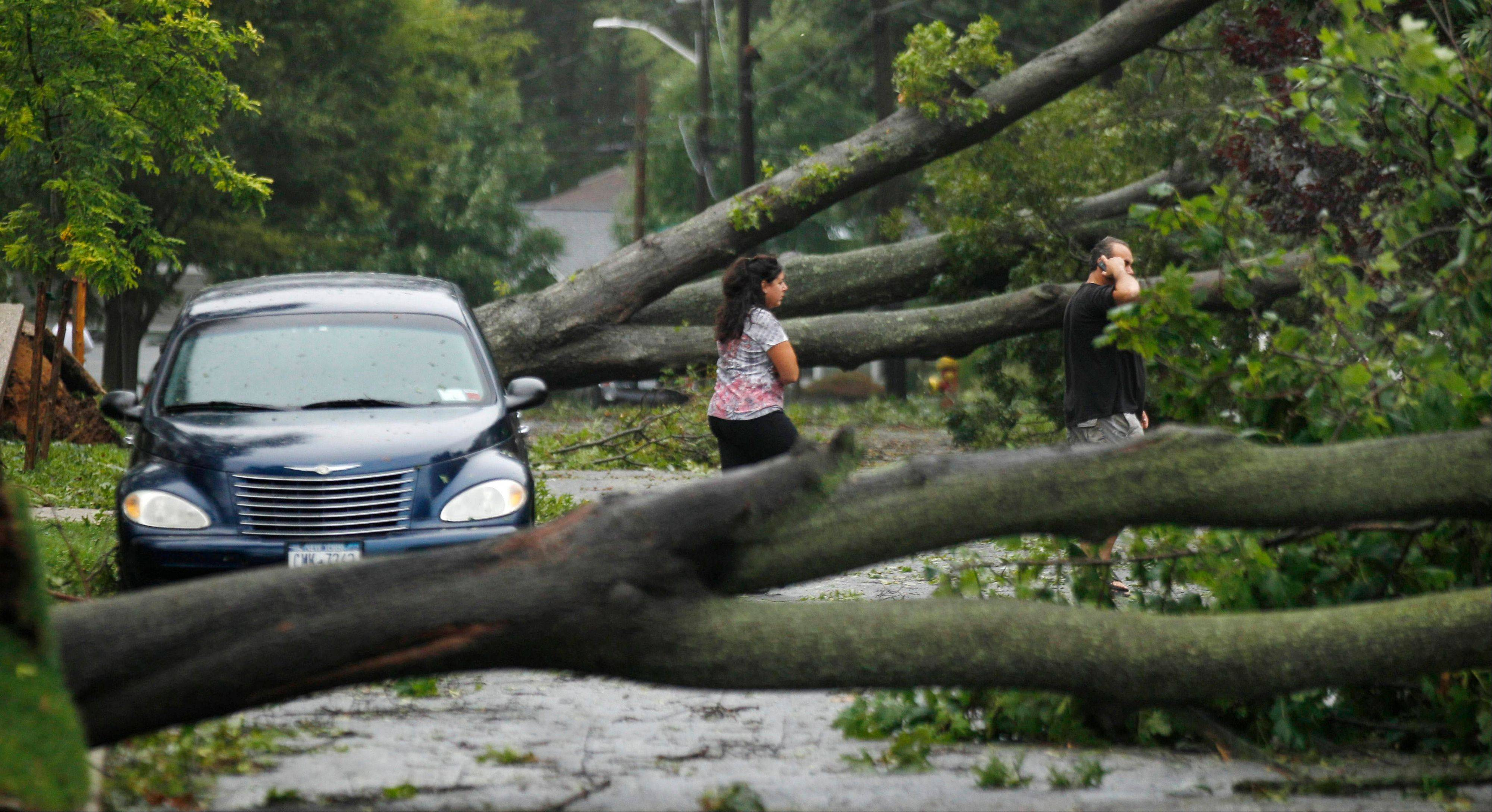 Two residents walk on their road which was not passable after the effects of Hurricane Irene dropped trees in their neighborhood in Massapequa, N.Y., on Long Island, Sunday, Aug. 28, 2011.
