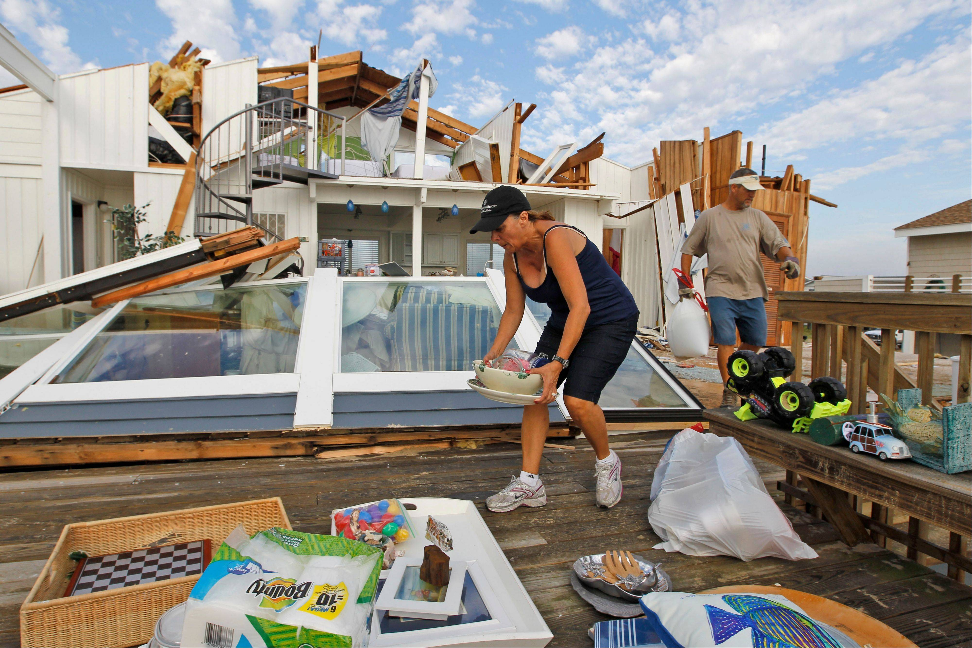 Denise Robinson, left, and Rich Brown, clear out belongings from her severely storm-damaged beach home in the Sandbridge area of Virginia Beach, Va., after Hurricane Irene hit the region, Sunday, Aug. 28, 2011. Irene inflicted scattered damage over such a broad area that the total damage -- and costs involved -- were not yet known.
