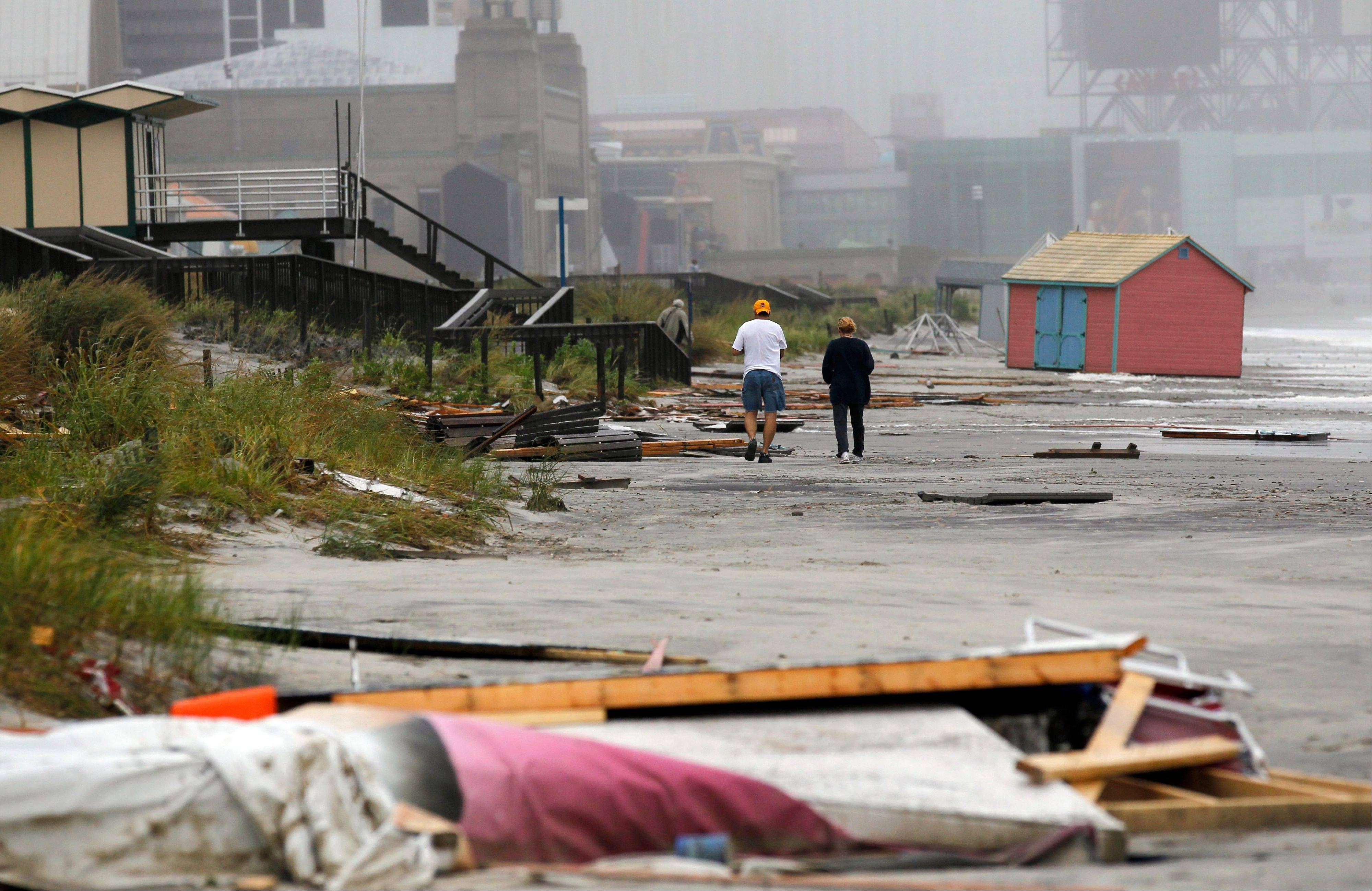 People along beach strewn with debris after Hurricane Irene swept the area, Sunday, Aug. 28, 2011, in Atlantic City, N.J.