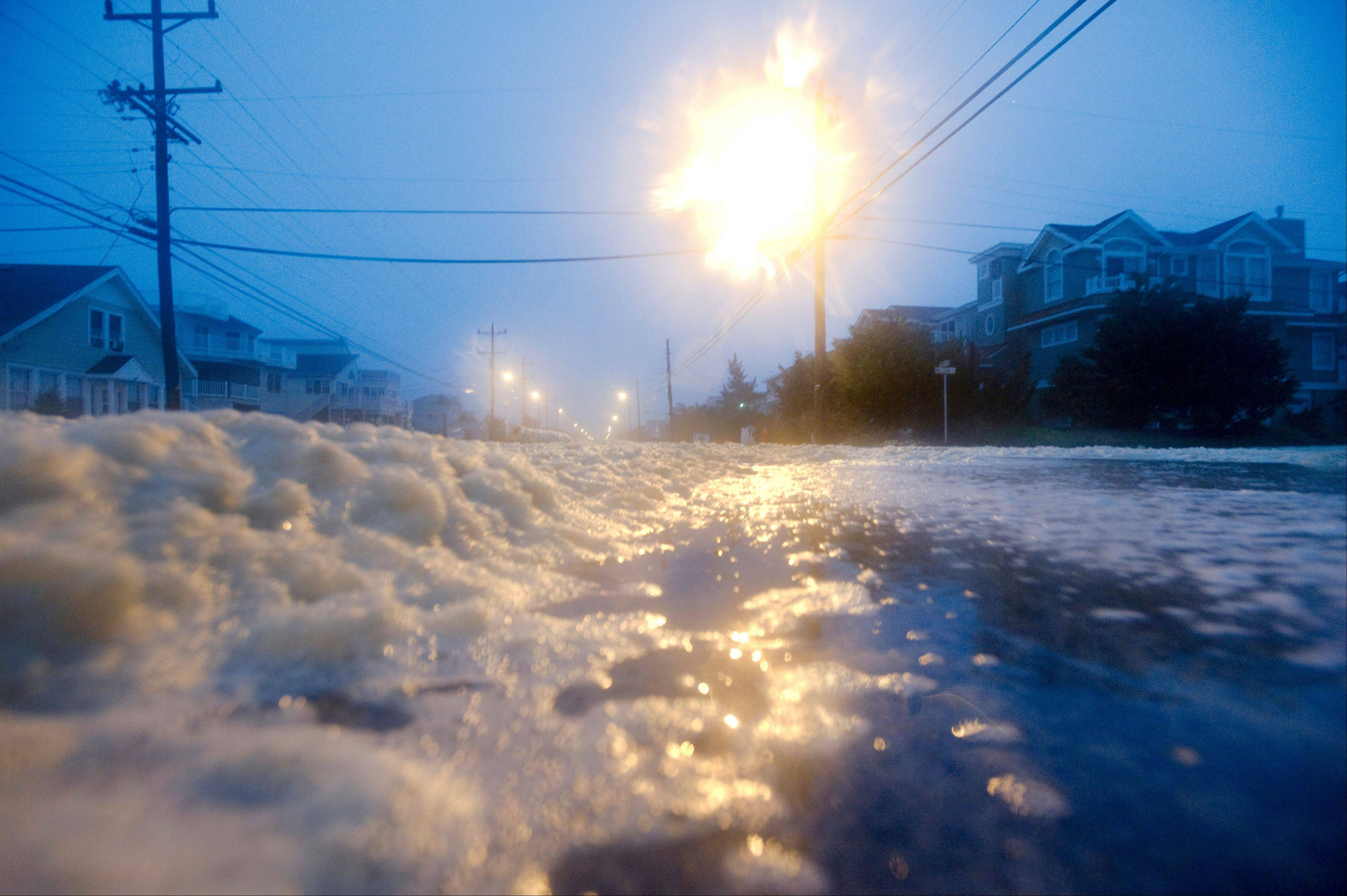 Sea foam floats across Bay Avenue as the surf from the Atlantic Ocean breaches the dunes on Nelson Street, Sunday Aug. 28, 2011 in Beach Haven, N.J.