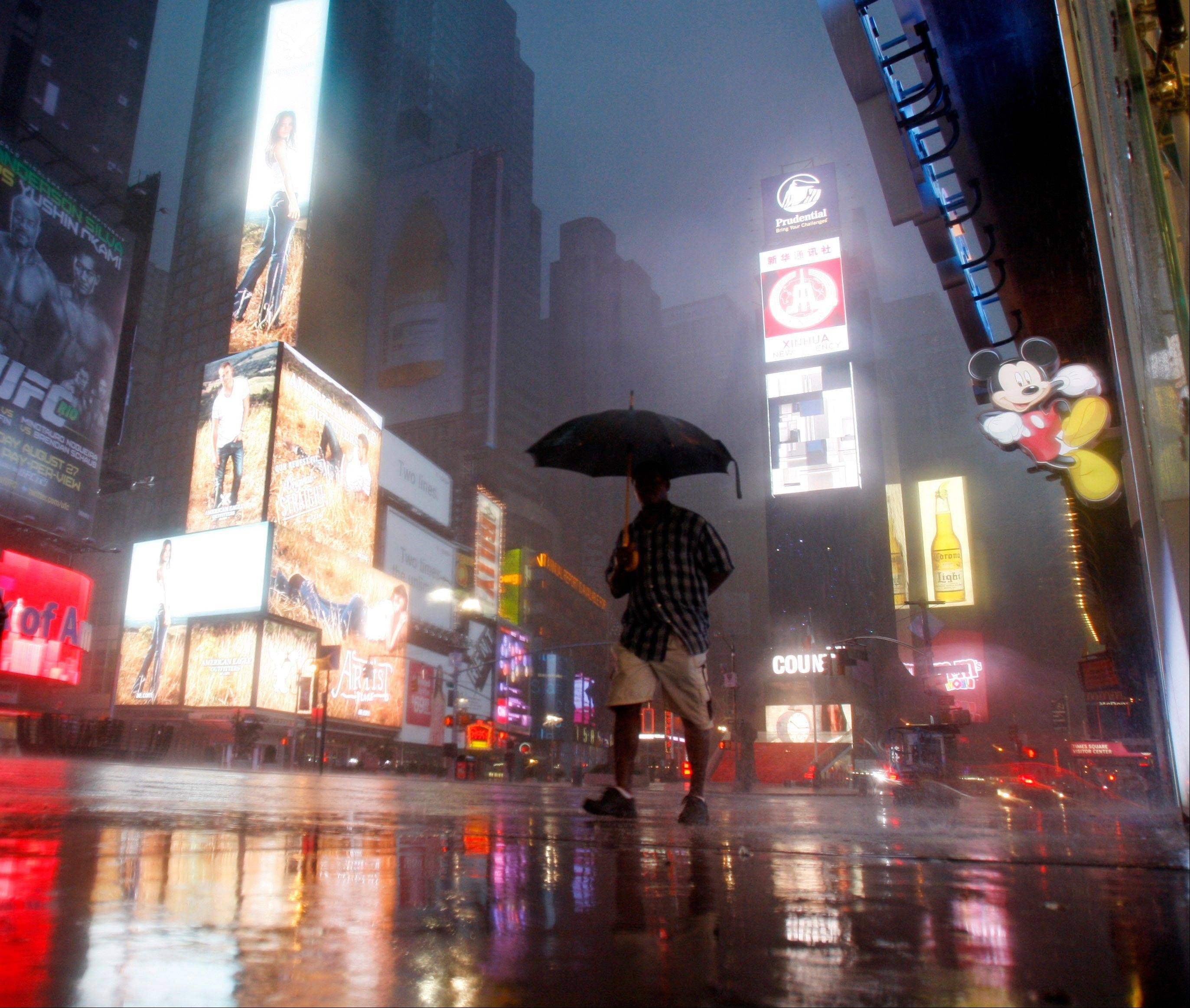 A man walks in Times Square as Hurricane Irene arrives in New York, on Sunday, Aug. 28, 2011.
