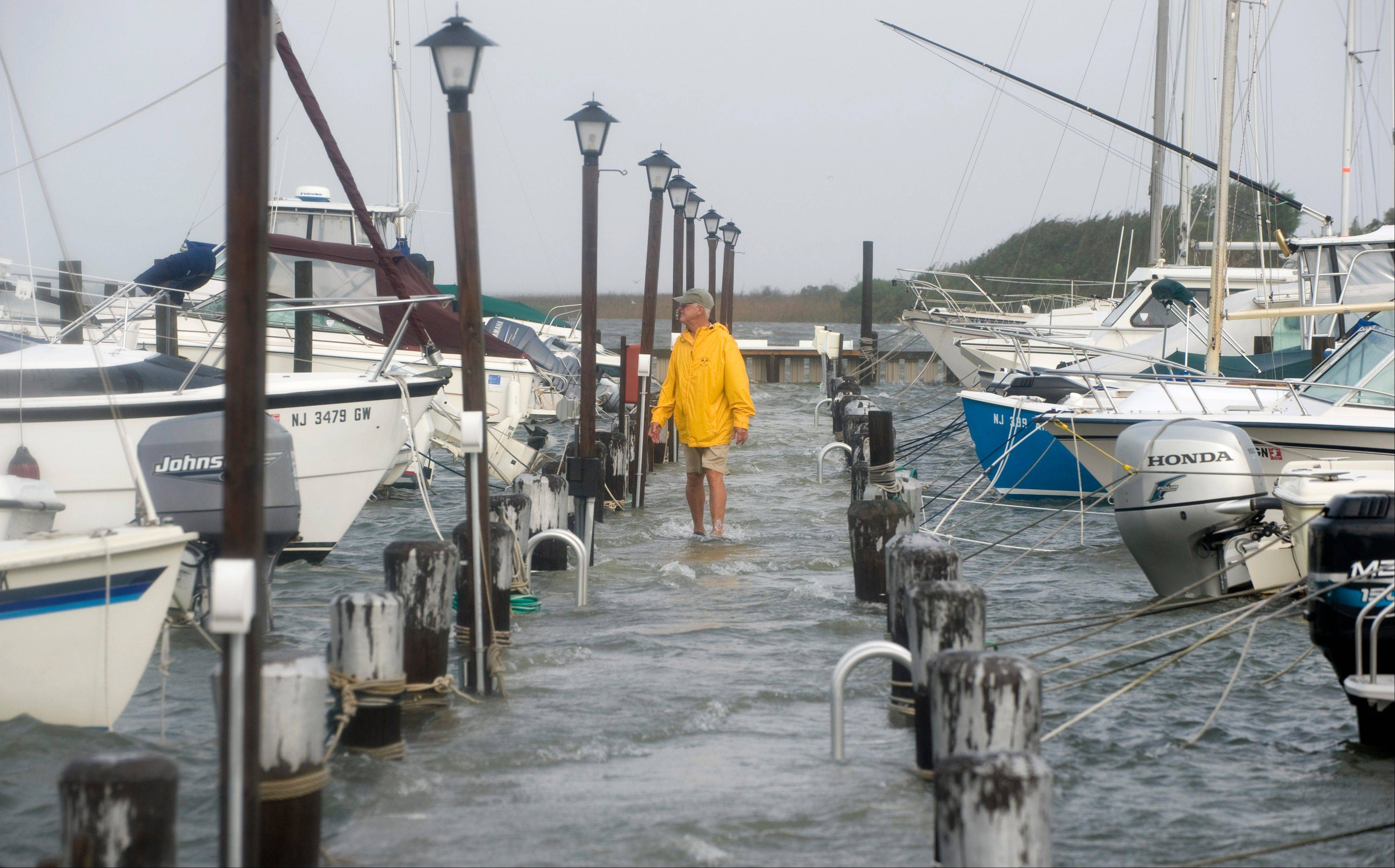 Robert Roy of Spray Beach, N.J., walks down one of the docks at the Spray Beach Yacht Club checking to make sure the boats are secure as the water in the bay rises from the tidal surge of Hurricane Irene on Long Beach Island, Sunday Aug. 28, 2011 in Spray Beach, N.J.