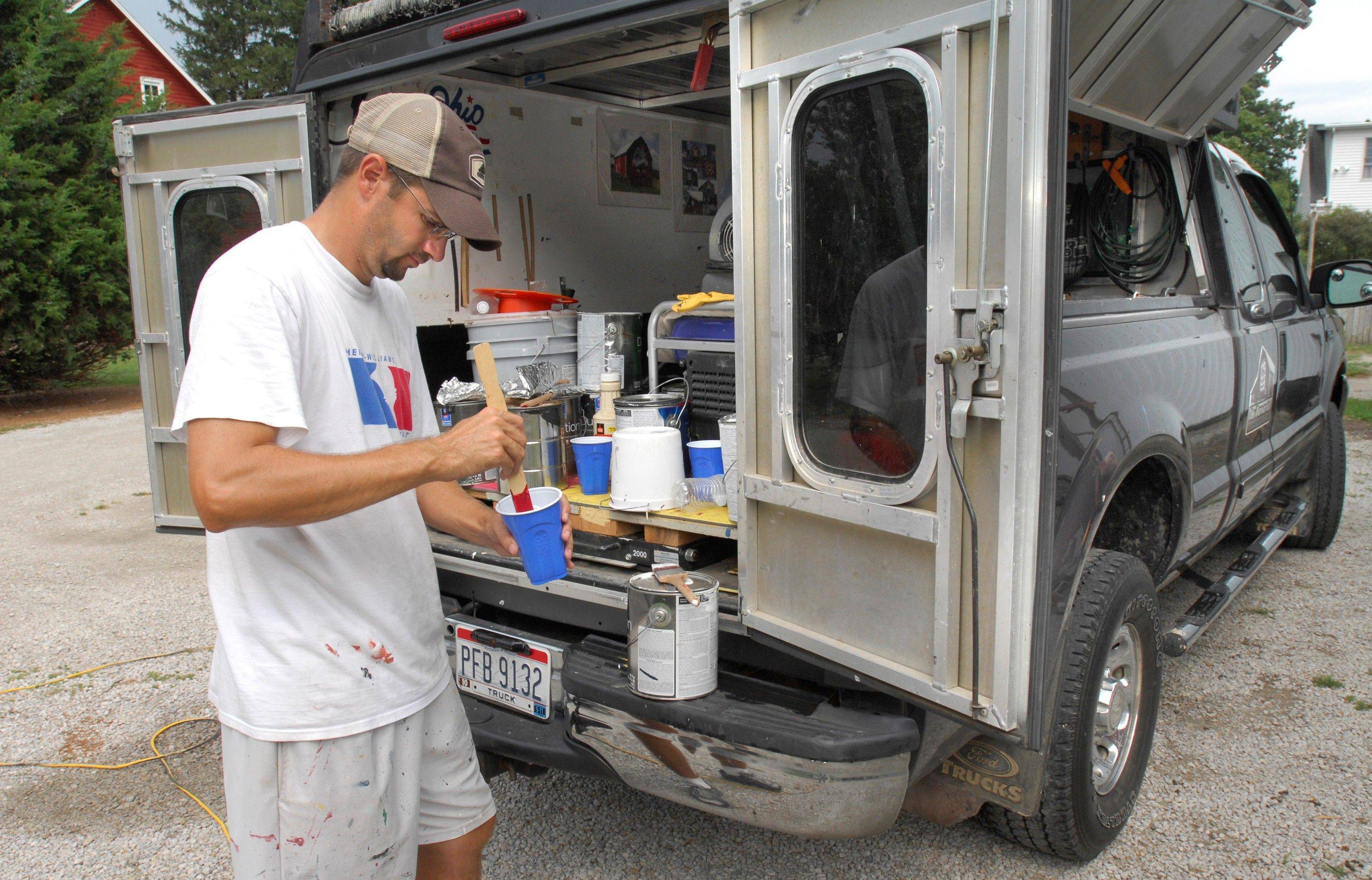 Scott Hagan mixes paint for a mural he was painting on Jo Morrison's barn east of Towanda, Ill. Hagan makes his living painting signs on barns and works out of his traveling studio as he performs commissions around the country.