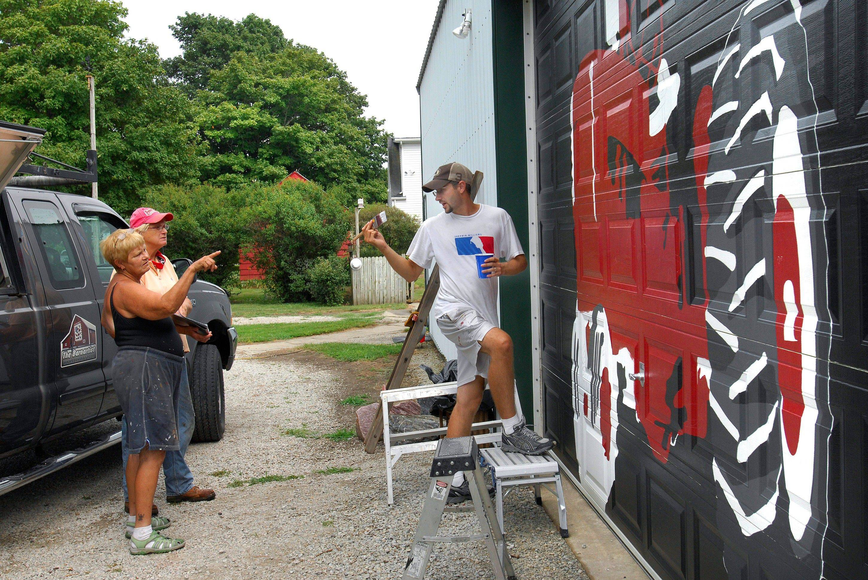 Jo Morrison, left, and her friend Donna Dubbelde talk with barn artist Scott Hagan while he paints a mural of a tractor on Morrison's shed door.