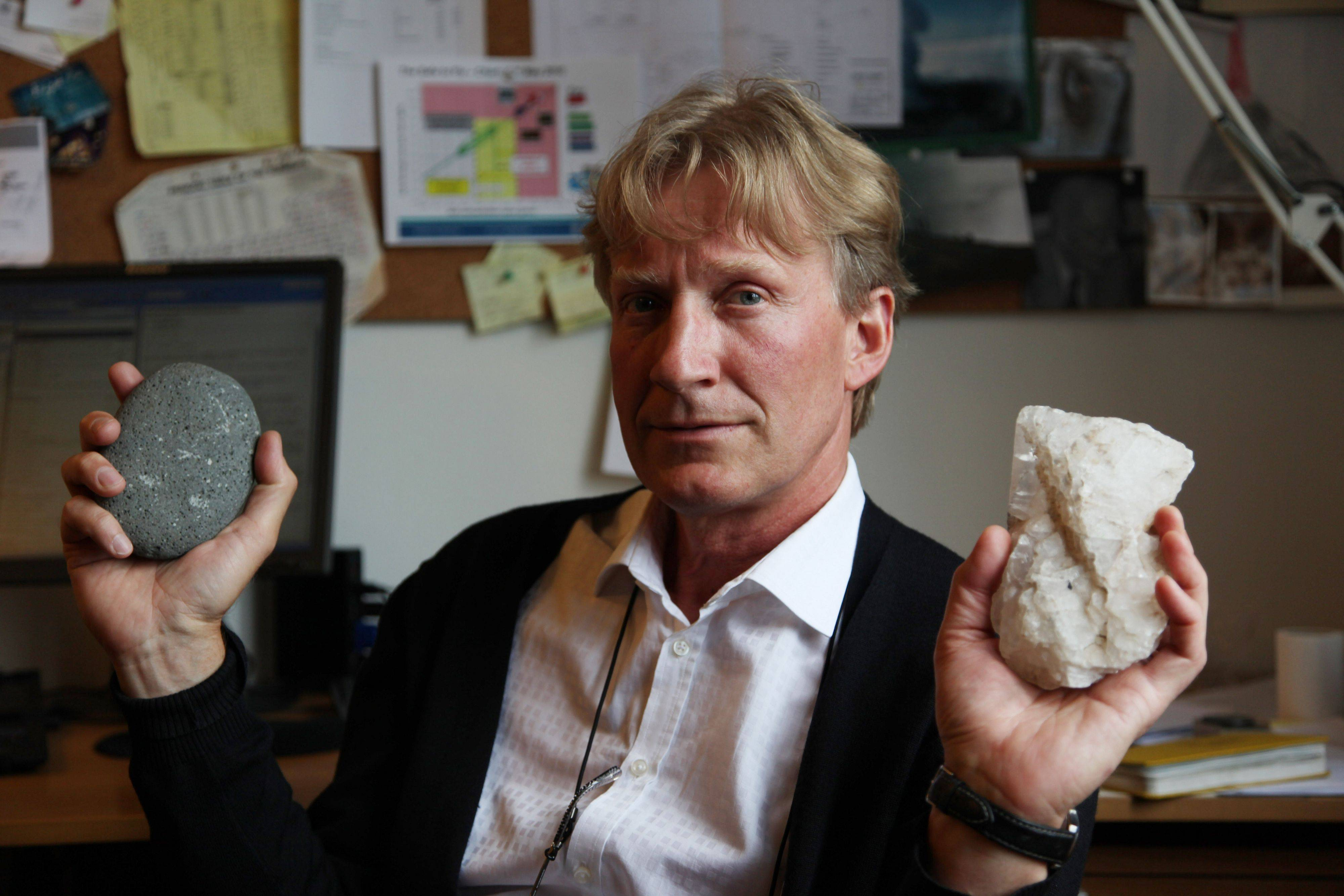 Geologist Sigurdur Reynir Gislason, the CarbFix experiment's chief scientist, holds examples of basalt rock, left, and limestone in his office at the University of Iceland in Reykjavik. At a nearby geothermal plant, CarbFix scientists will separate carbon dioxide from a volcanic field's steam and pump it underground to react with porous basalt, forming limestone, to see how well the gas most responsible for global warming can be locked away in harmless form.