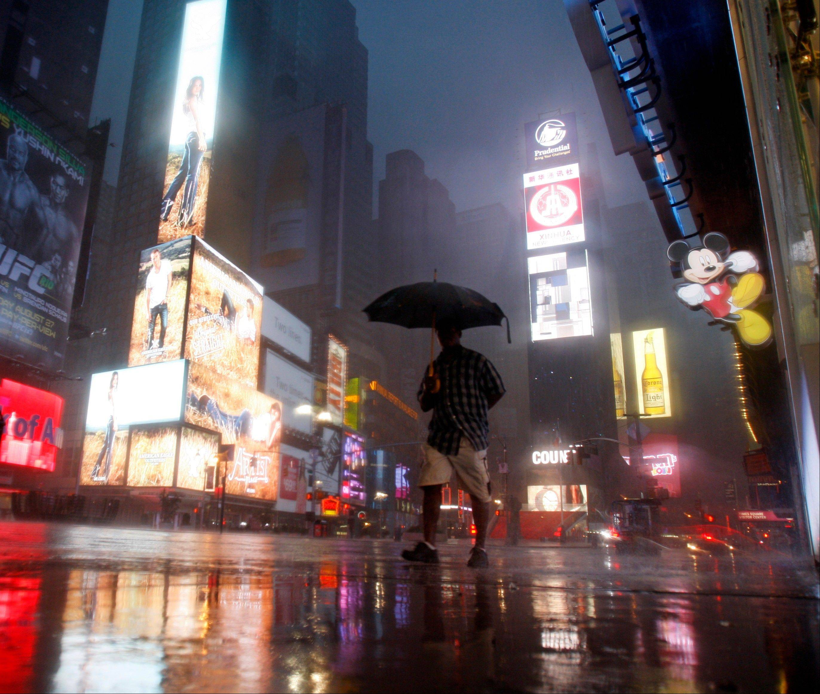 A man walks in Times Square Sunday as Hurricane Irene arrives in New York City.