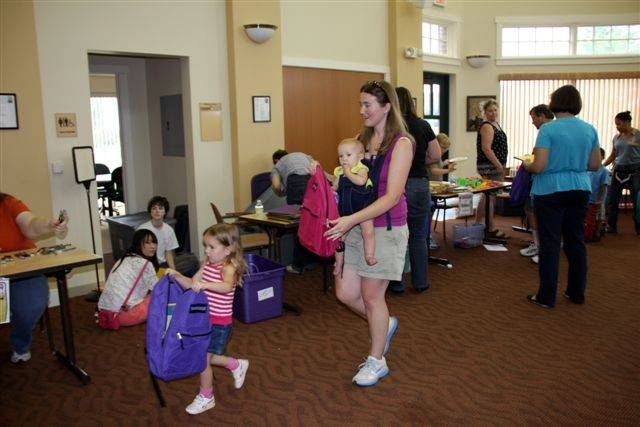 Cecelia Ochs, left, Eva Ochs, in baby carrier, and Michelle Ochs, all of Carpentersville, are among 80 volunteers.
