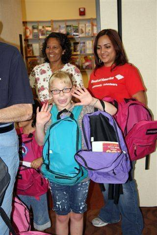 Emma Davenport, front, of Hanover Park, helps stuff the backpacks.