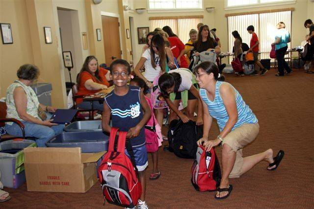 Spencer Benson, left, and his mom, Karen, right, of Streamwood, pitch in to fill backpacks for the Backpack Buddies Club.