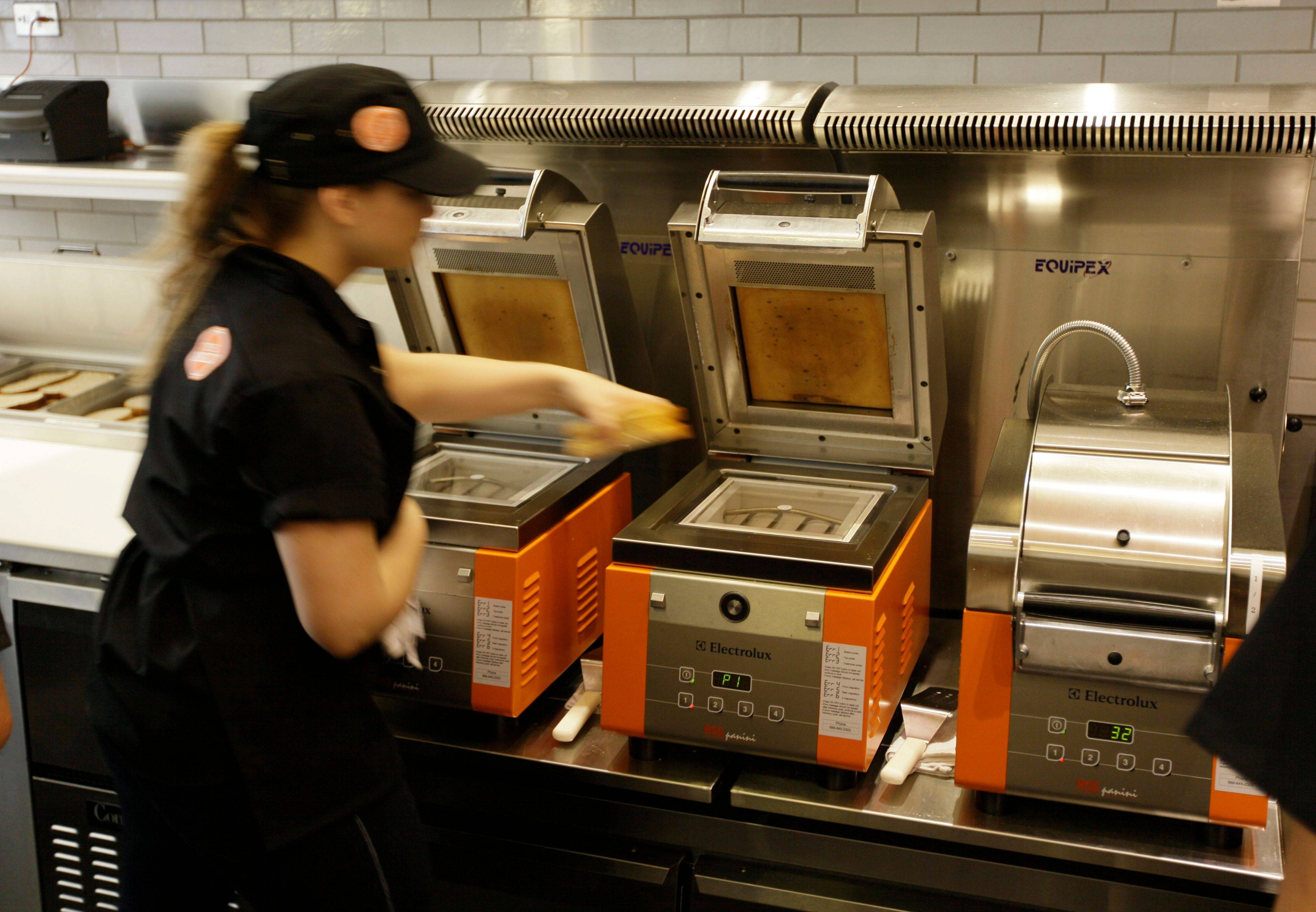 A crew member places a sandwich onto an Electolux grill at The Melt in San Francisco. Owner Jonathan Kaplan ís starting a grilled cheese restaurant business that combines fast food with high tech.