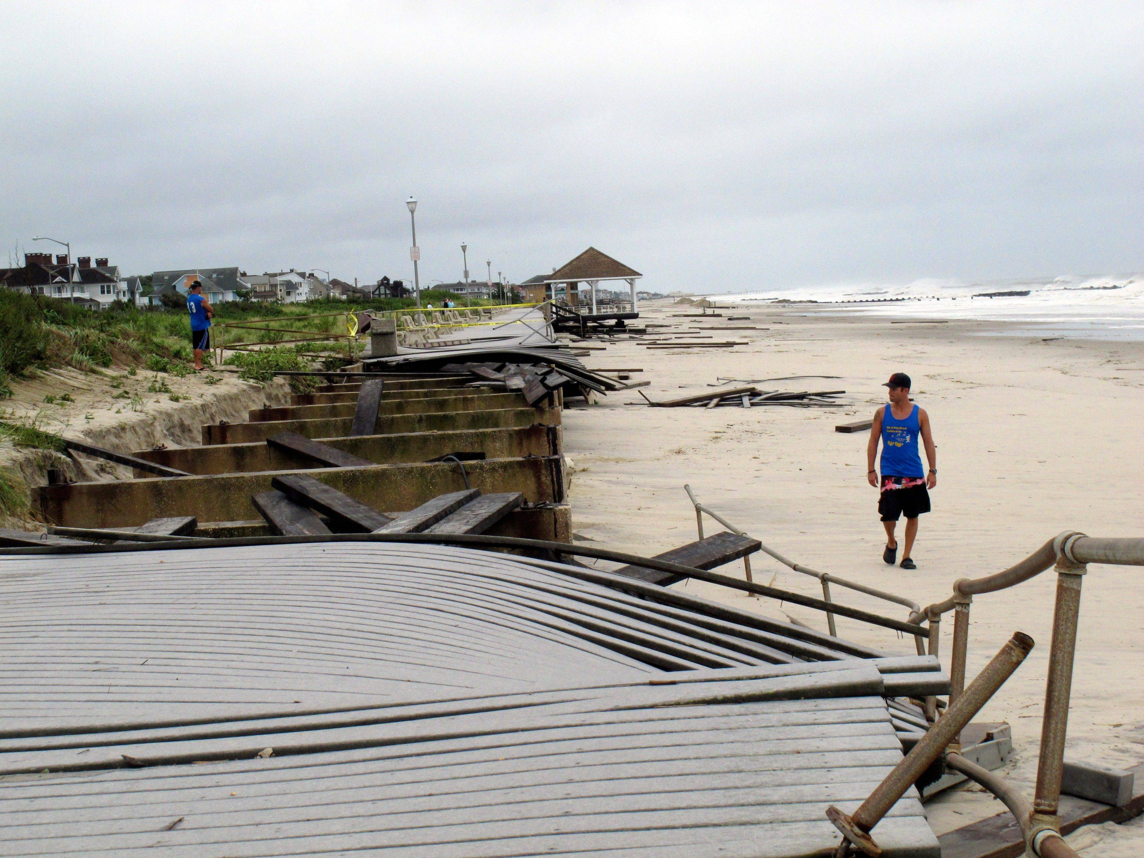 Spectators look at the ruined boardwalk in Spring Lake, N.J., hours after Hurricane Irene damaged most of the two-mile walkway.