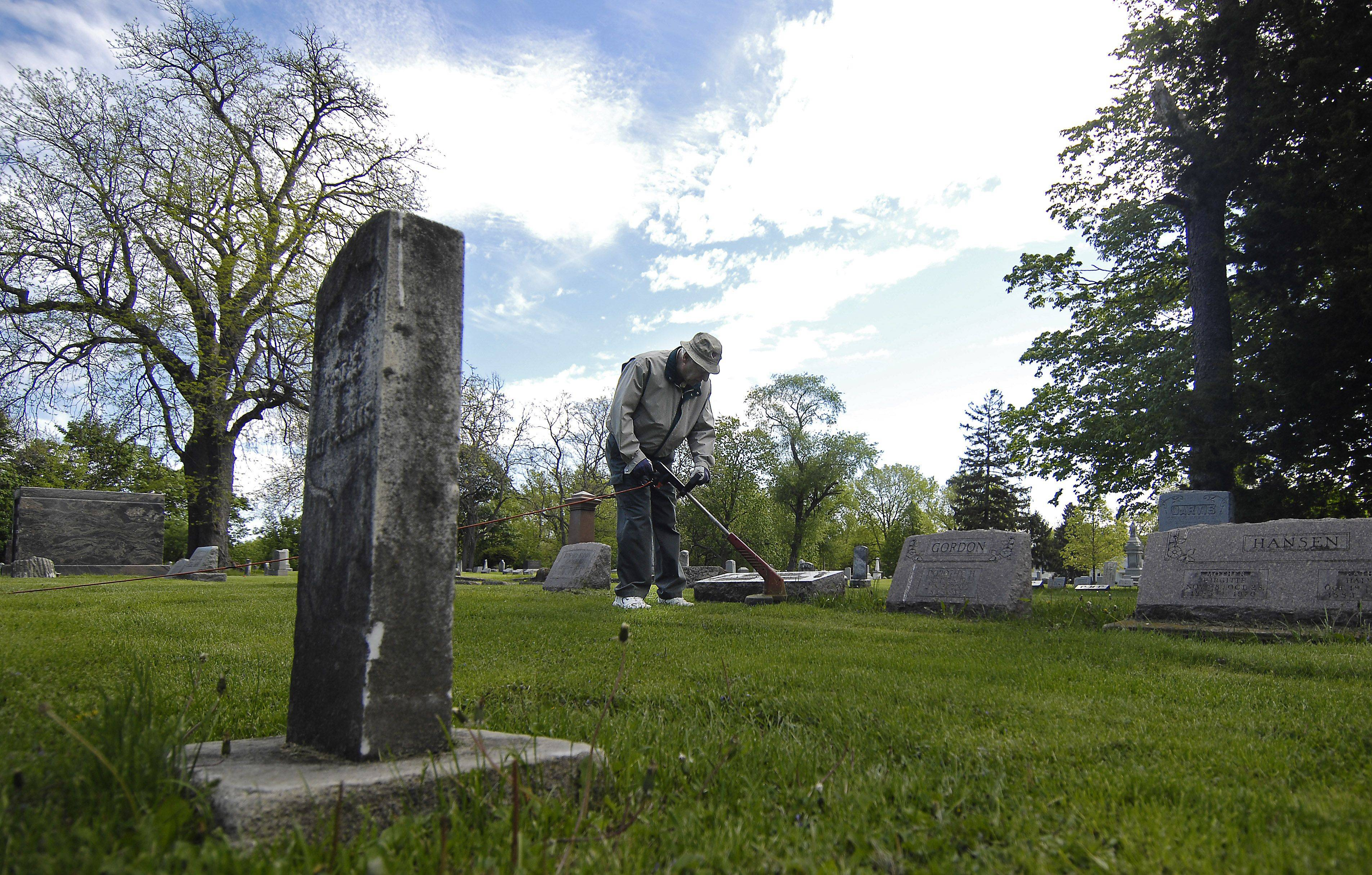 Alderman Ron Singer of Geneva trims around headstones as he works with a couple of other volunteers, including Alderman Sam Hill (not pictured) to clean up the West Side Cemetery earlier this year.