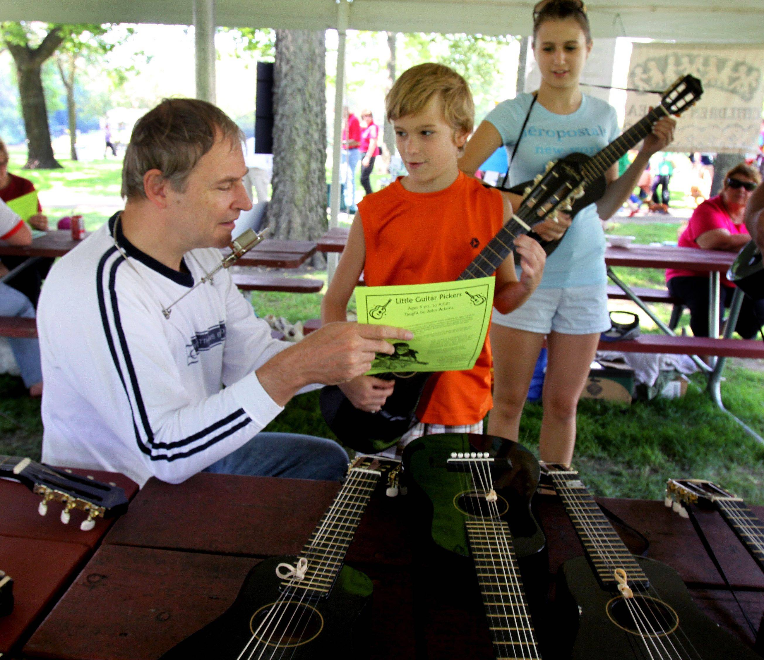 John Adams, left, from the Little Guitar Pickers program, gives a lesson to Brandon Godfrey, 9, and his sister Ashley, 14 of Batavia at the 33rd annual Fox Valley Folk Music and Storytelling festival in Geneva.