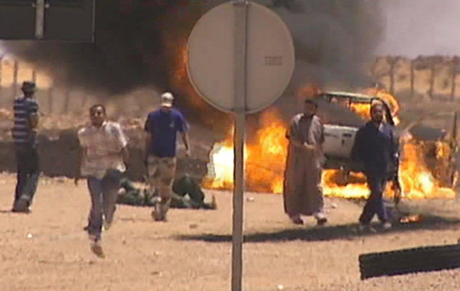 A blazing pickup truck driven by two Gadhafi soldiers, one of them the man on floor near the vehicle, on a recognizance mission that came under fire by Libyan rebels on the front line, 86 miles from Sirte, Libya, Monday.
