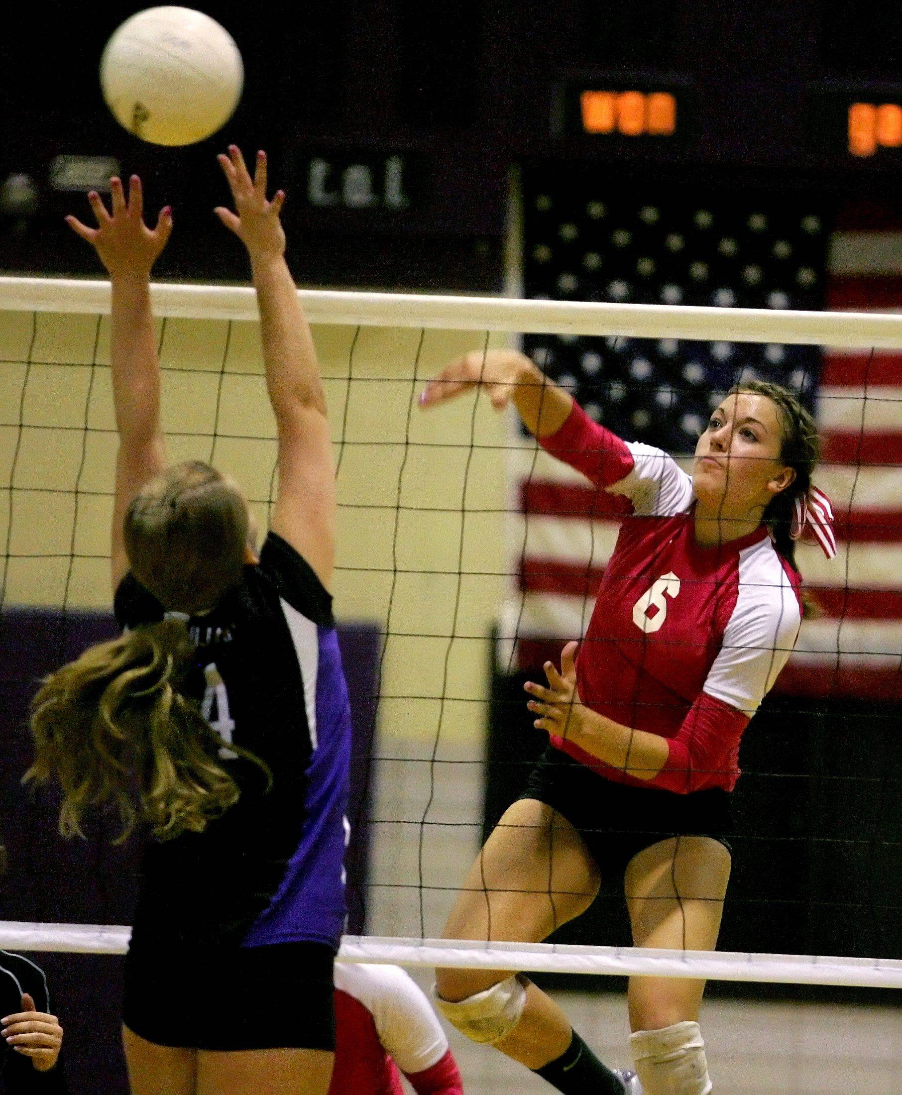 Alysia Baznik of Naperville Central hits the ball past Katie Canning of Downers Grove North in girls volleyball action Tuesday in Downers Grove.