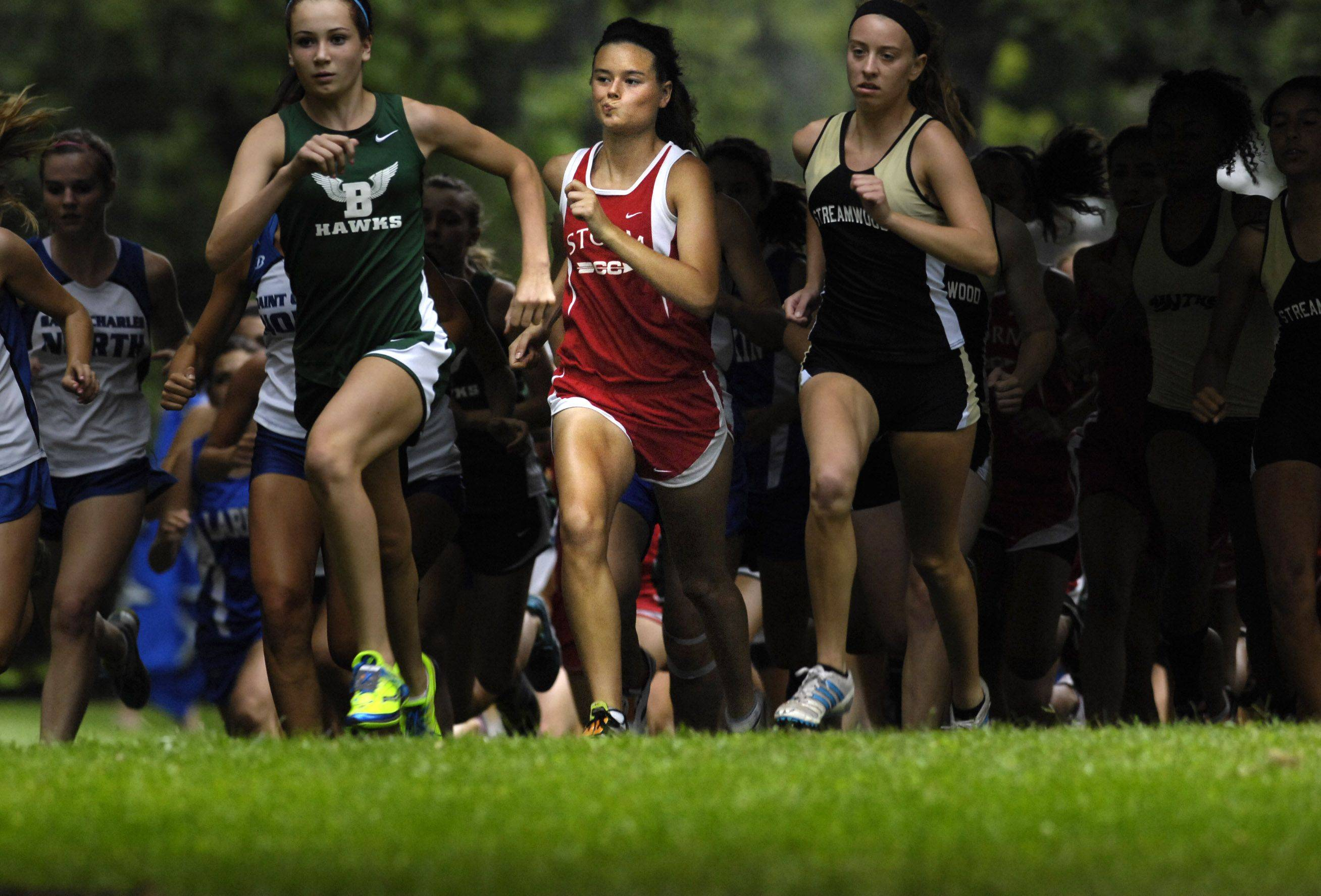 South Elgin's Jordan Tuin, middle, bites her lip as she comes out of the shadows at the start of the Elgin cross country invitational Tuesday at Lords Park. She finished second overall. To her left is Amanda Patterson of Streamwood, who finished fourth, and on her right is Bartlett's Nicole Watkins, who finished fifth overall.