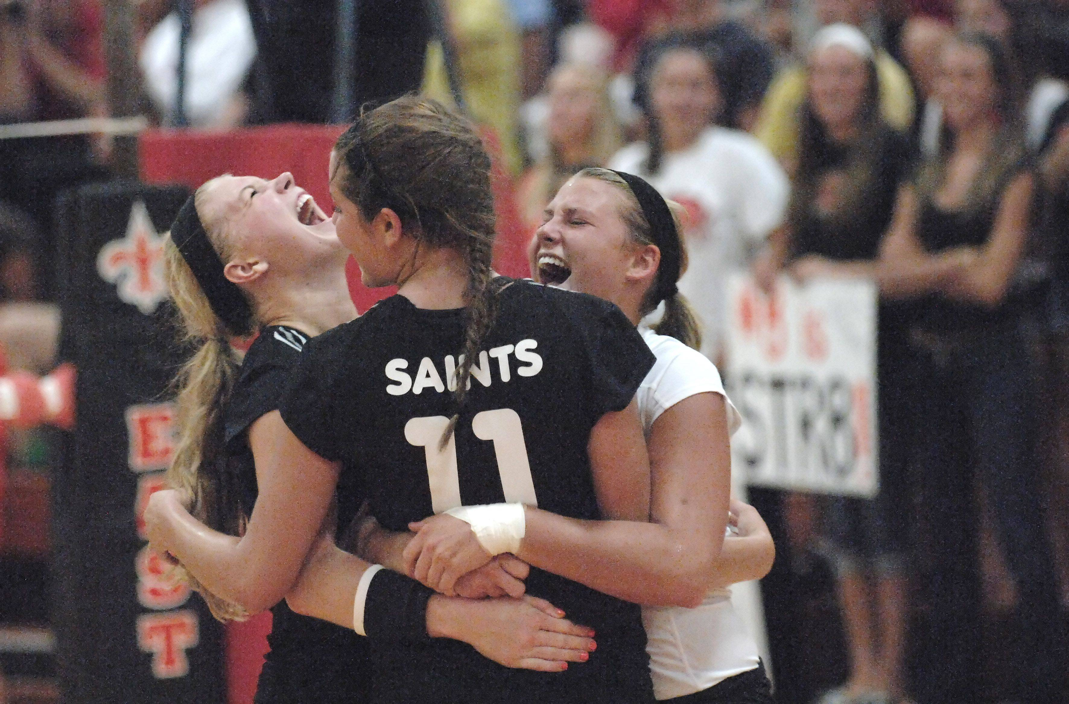 St. Charles East's Kadie Brooks, Erienne Barry and Maisey Mulvey celebrate a point early in the first game against Benet Academy Tuesday.