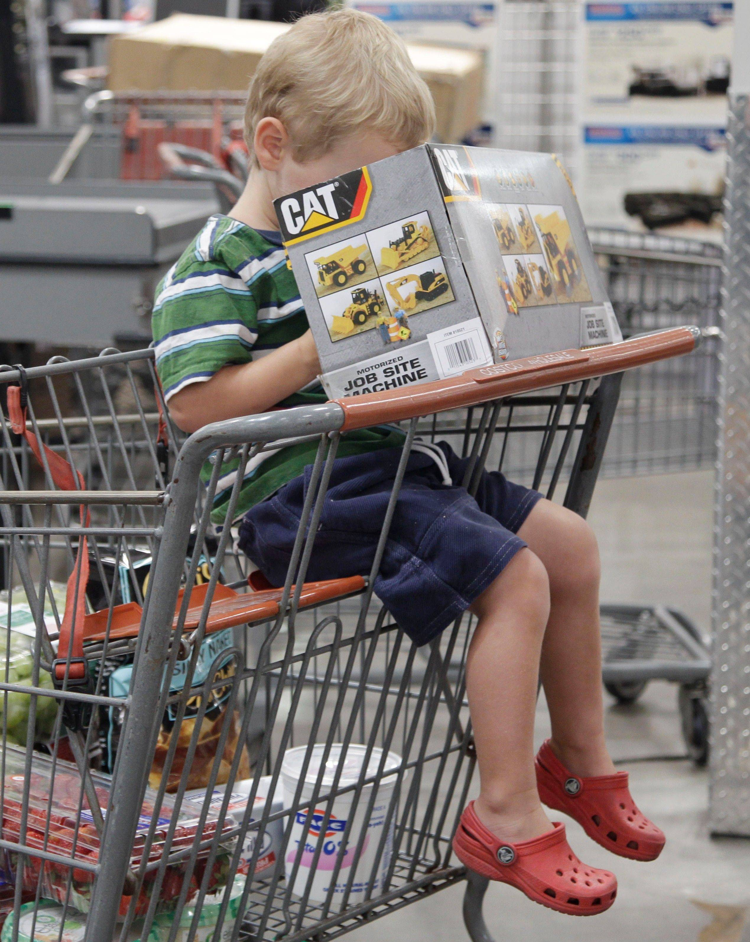 A young shopper peers into a box as he waits to get through the check-out at a California. A private research group said Tuesday that consumer confidence in the economy in August dropped almost 15 points to the lowest level since April 2009 . $PHOTOCREDIT_ON$  $PHOTOCREDIT_OFF$