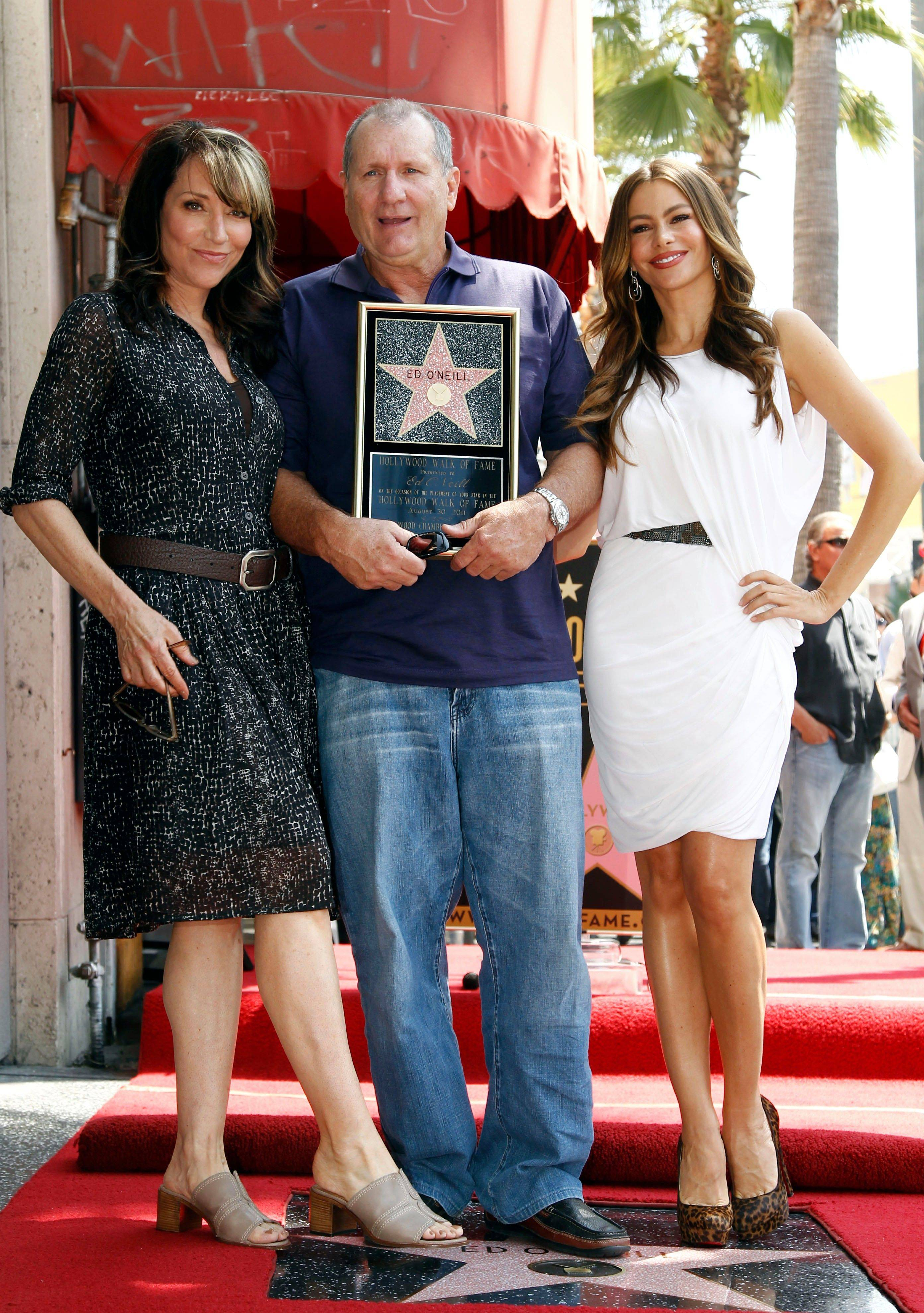 "Actor Ed O'Neill, center, poses with actress Katey Sagal, left, who played his wife in the Fox series ""Married with Children,"" and Sofia Vergara, who currently plays his wife in the ABC comedy ""Modern Family"" Tuesday after receiving a star of the Hollywood Walk of Fame in Los Angeles."