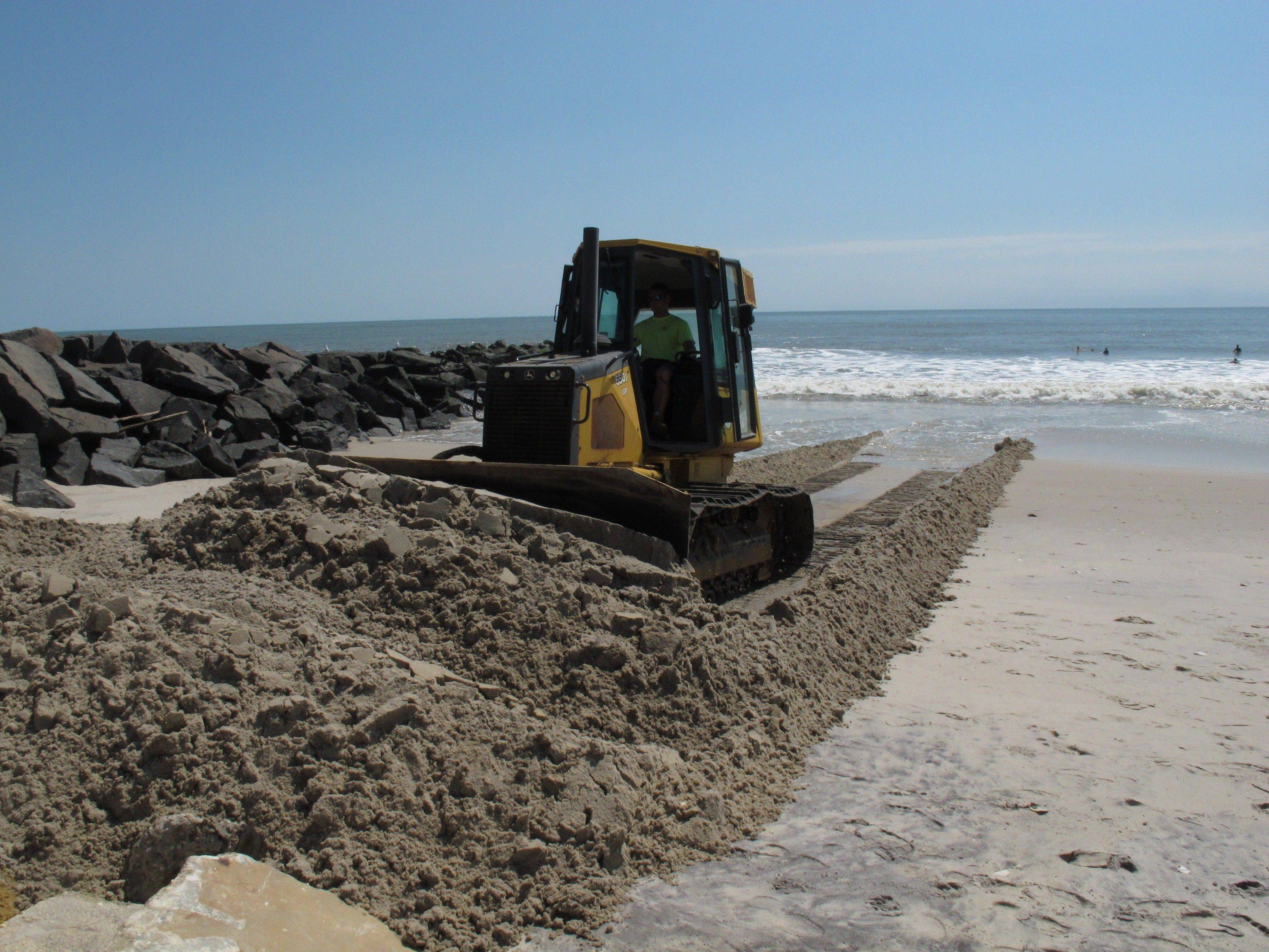 A worker uses a bulldozer to push sand away from the ocean toward badly eroded dunes in the Holgate section of Long Beach Township, N.J.