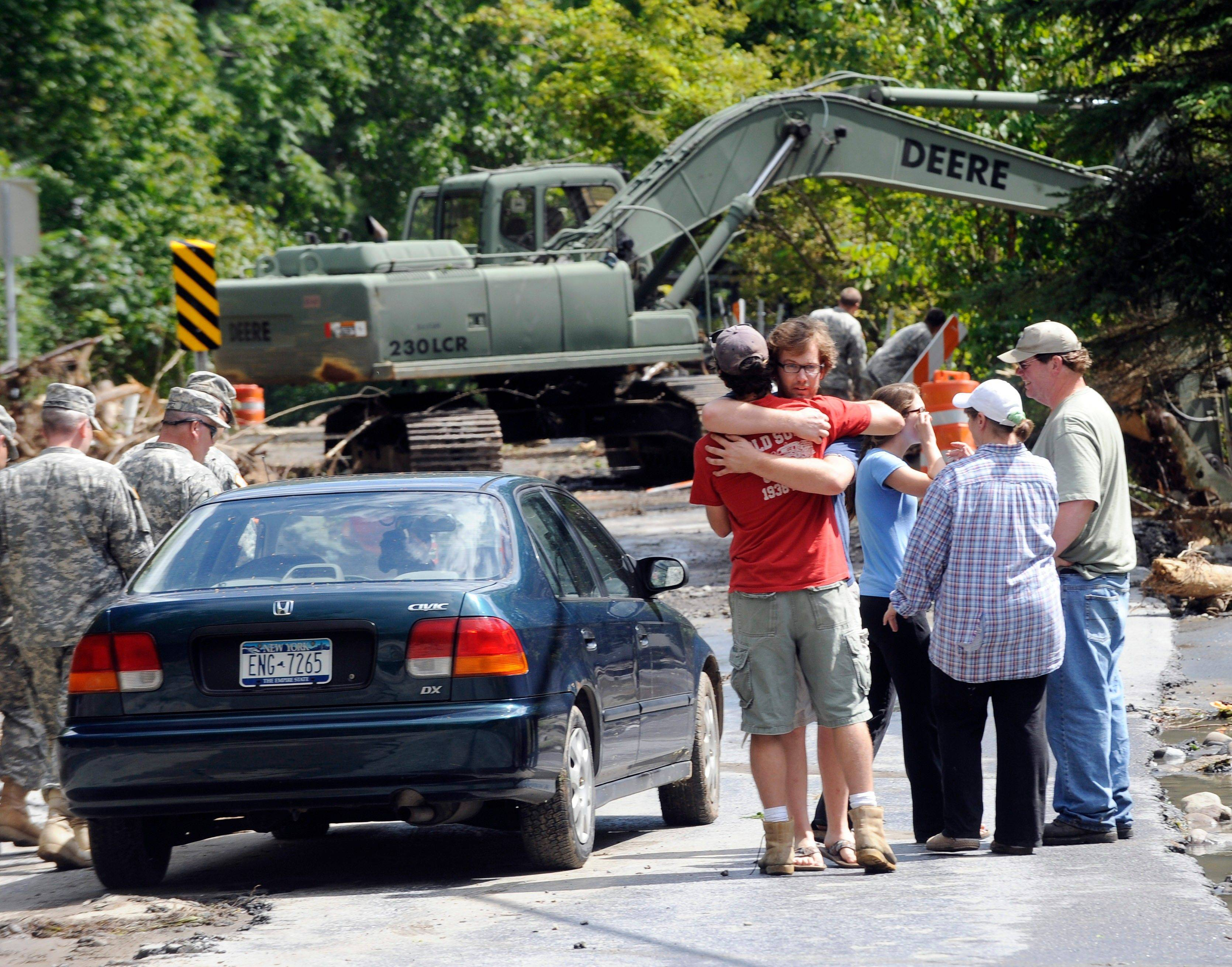 Members of the Quinn family, right, embrace outside their home while members of the New York National Guard use heavy equipment to clear debris from a stream that destroyed their family printing business in Middleburgh, N.Y., Tuesday.