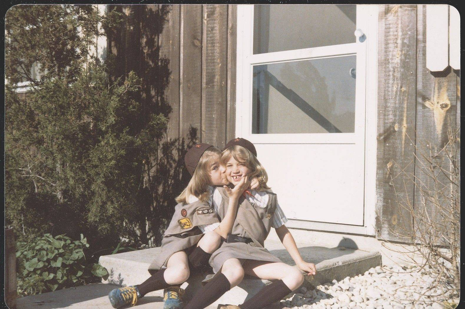 Dressed in their Brownie uniforms, Denise Richards gives her sister, Michelle, a kiss on the doorstep of their Mokena home.