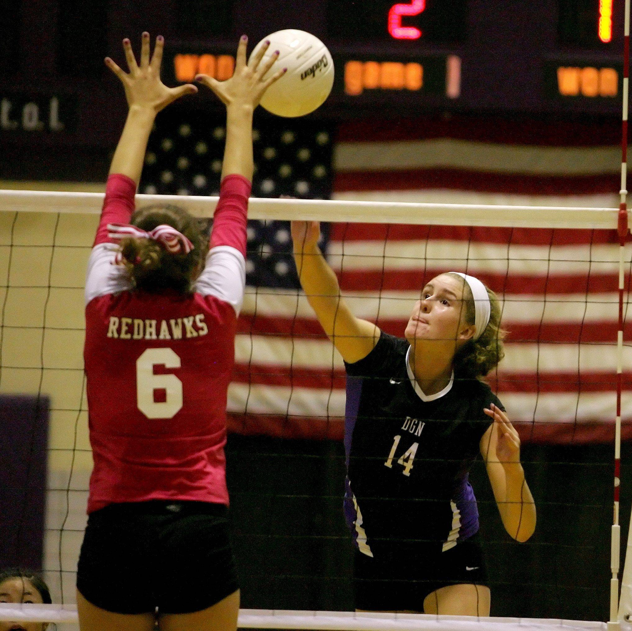 Alysia Baznik of Naperville Central, left, goes up to block a shot by Jessie Tulacka of Downers Grove North in girls volleyball action Tuesday in Downers Grove.
