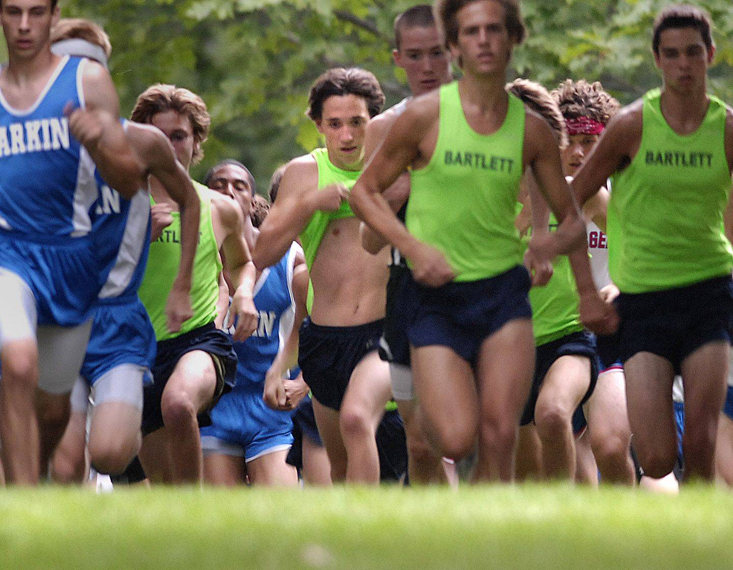 Eventual second place finisher Joey Salatino of Bartlett lifts his jersey in the starting sprint during the Elgin cross country invitational Tuesday at Lords Park.