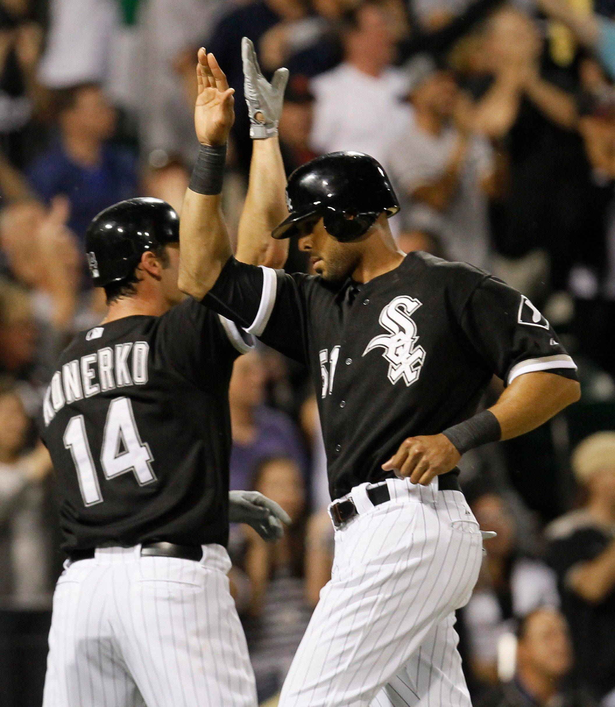 Paul Konerko, left, and Alex Rios celebrate after scoring on a throwing error by Minnesota Twins right fielder Michael Cuddyer off a ball hit by Alejandro De Aza Tuesday during the fifth inning.