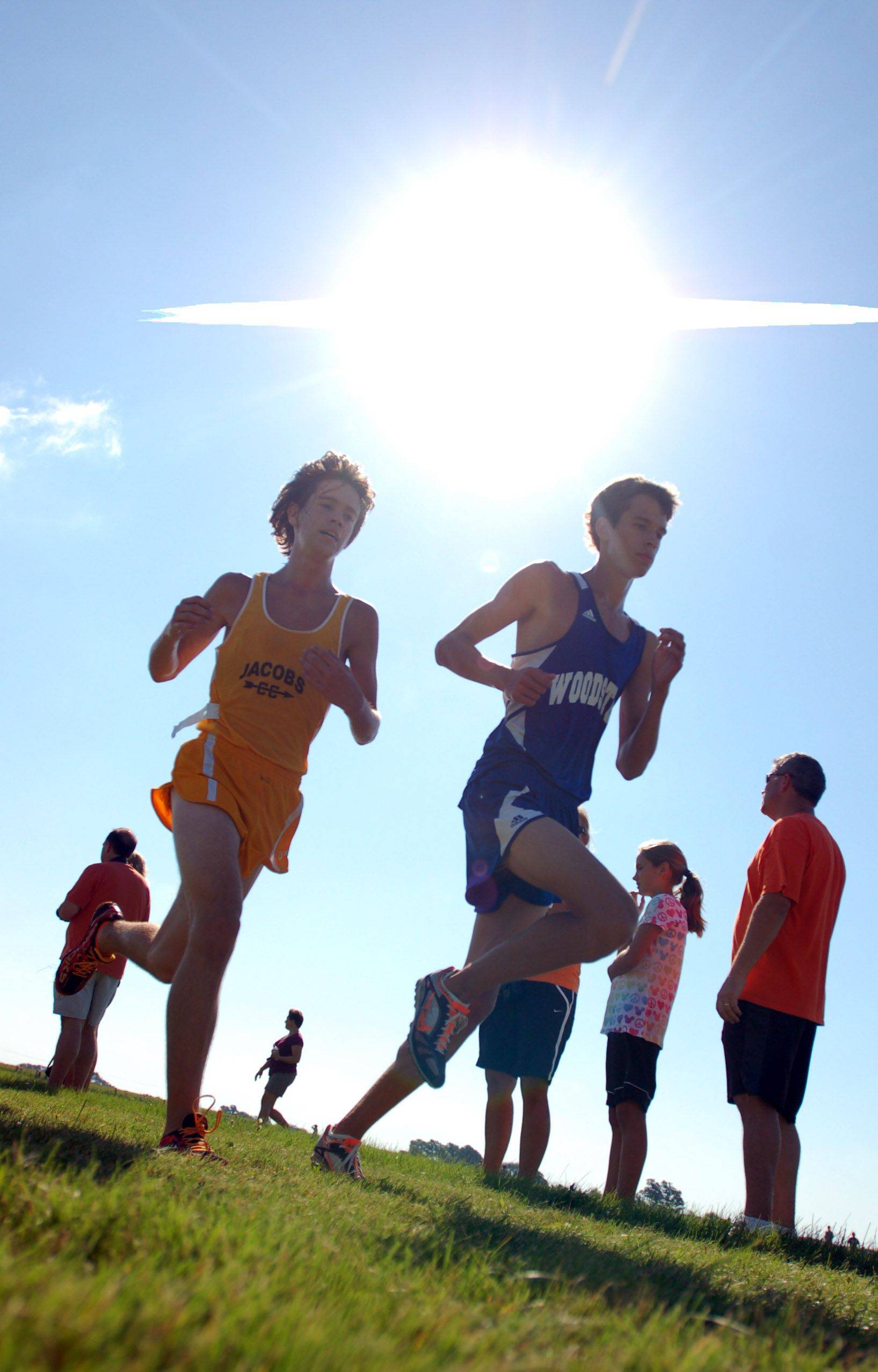 Jacobs' Zach Johnson catches up to Woodstock's Tim Semmen during the McHenry County boys cross country meet at Huntley High School Saturday.