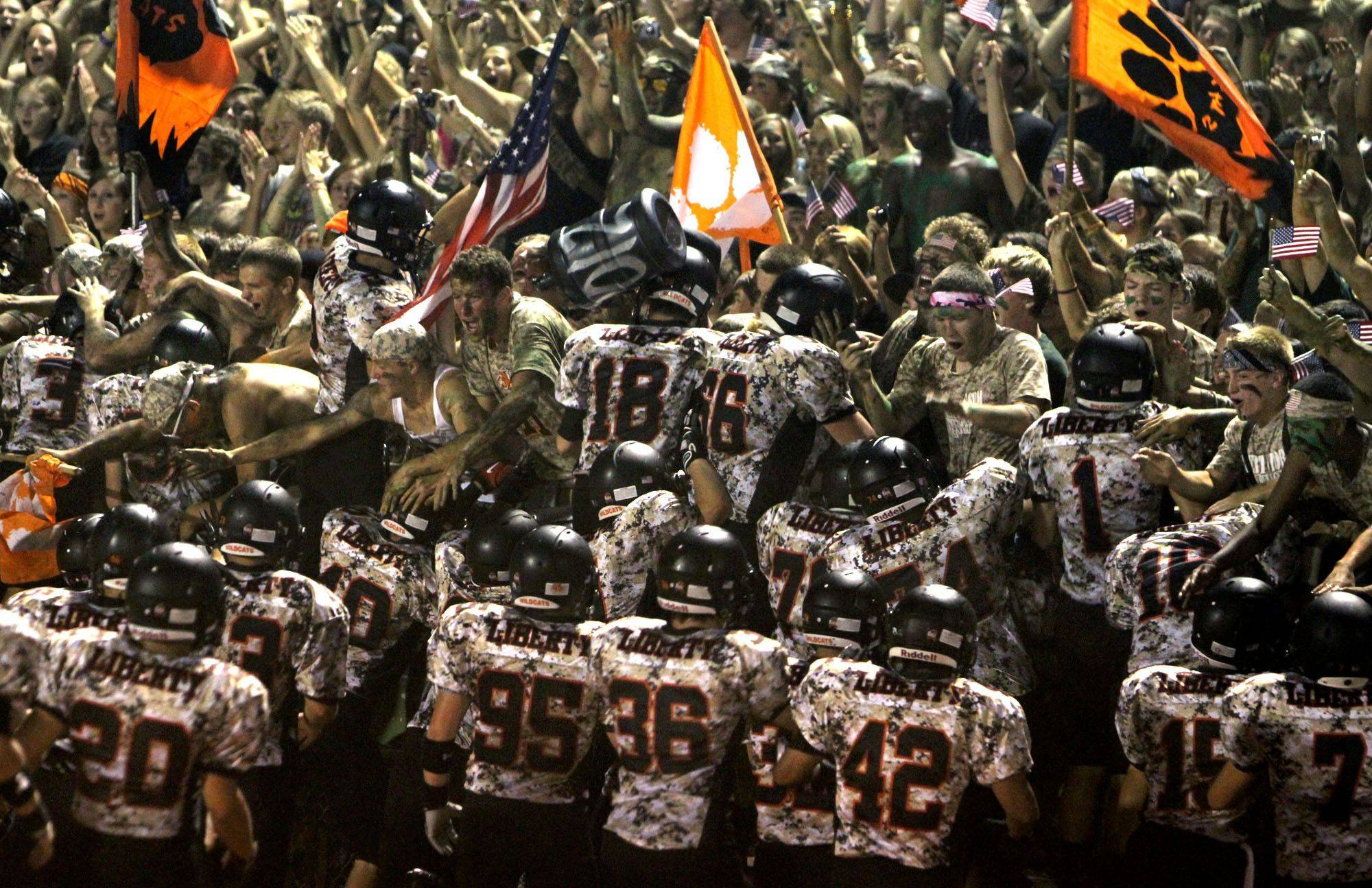 Libertyville players, wearing camouflage uniforms, leap into the stands after taking the field on military appreciation night Friday.