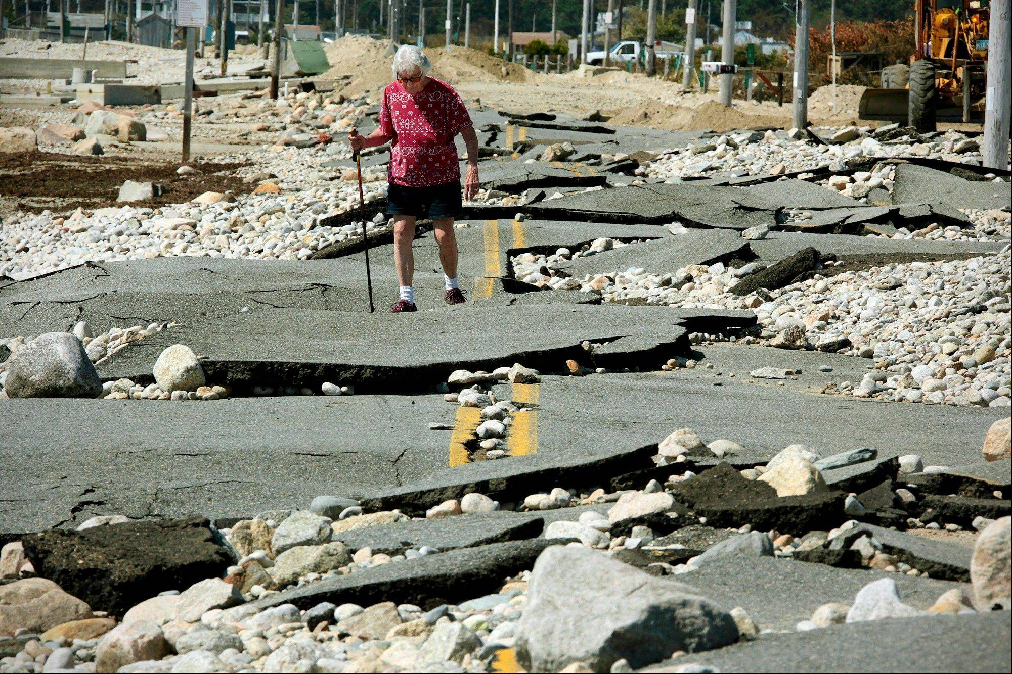 Pat Richard tries to make her way along what remains of East Beach Road in Westport, Mass., Wednesday. The beach-front road was shattered by high surf and winds when Tropical Storm Irene swept the area on Sunday.