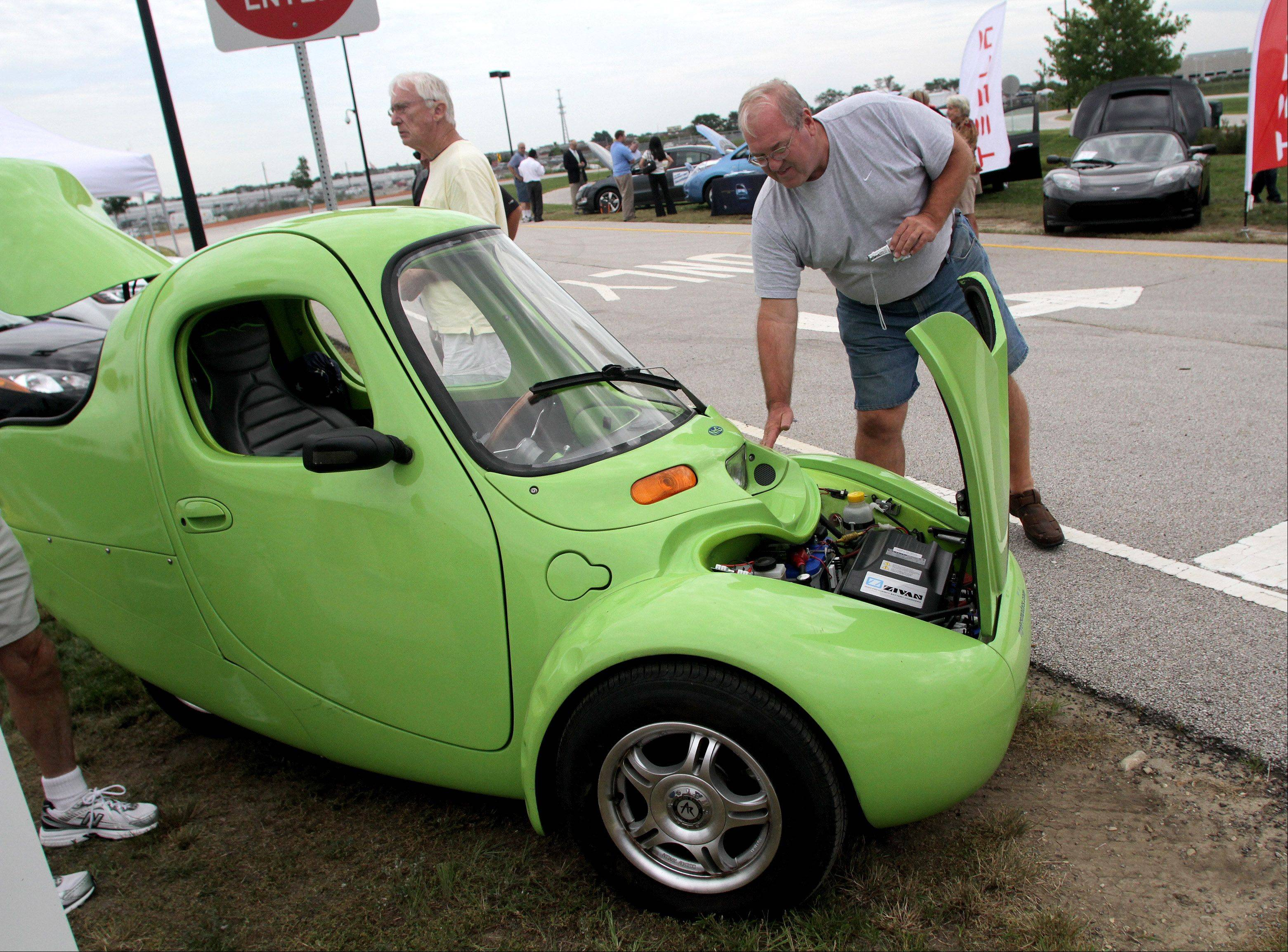 Dan Ferraro of Carol Stream checks out an all-electric car called N.m.G. (no more gas) made by Myers Motors. It was on display at the Green Car Show at the Naperville Test Track Tuesday in Naperville.