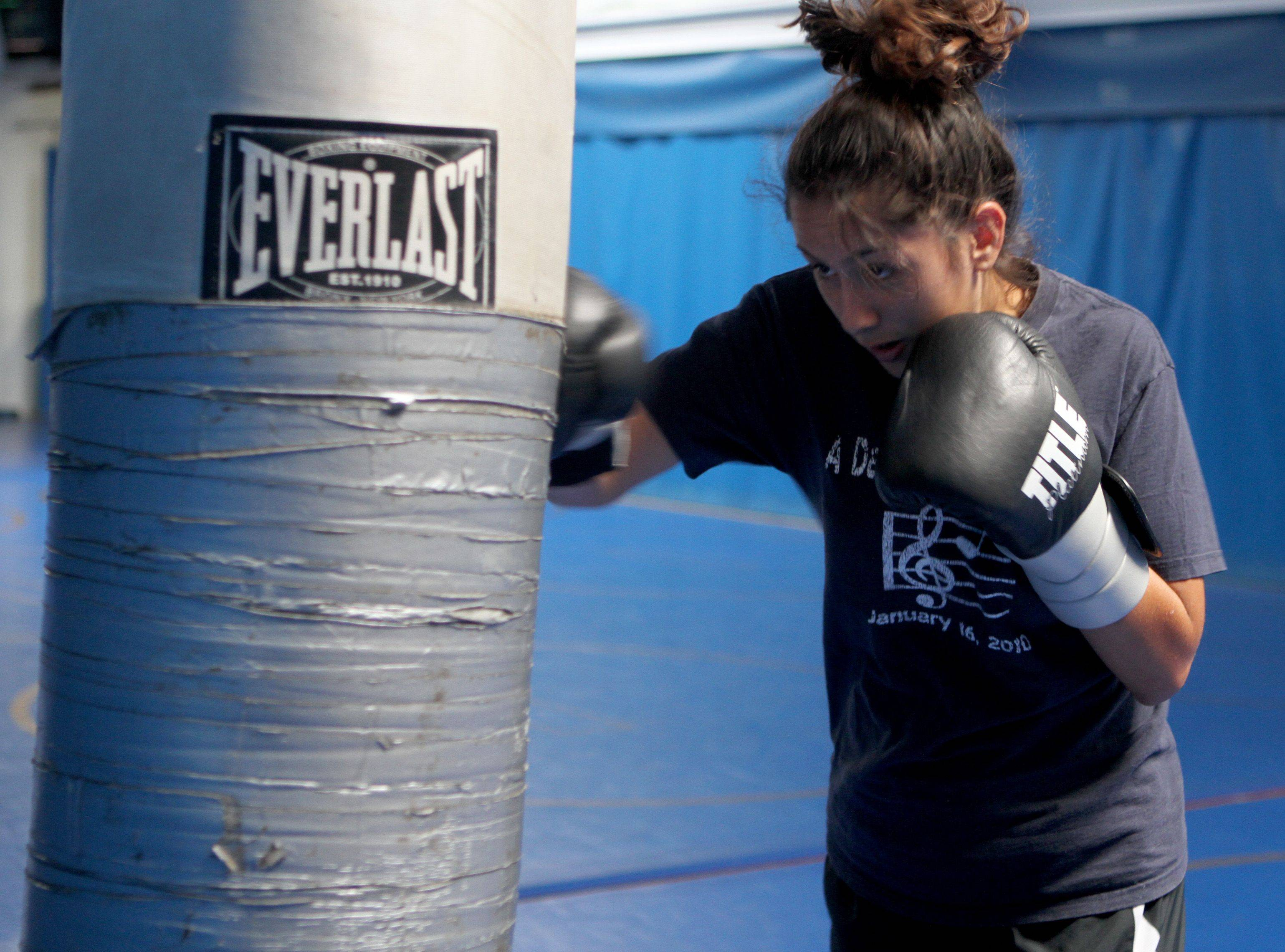 Maribel Aguilar, a junior, practices with a punching bag during boxing club practice at Wheeling High School. This fall marks the fourth year of the club started by Mike Burke, who is also an English teacher at the school.
