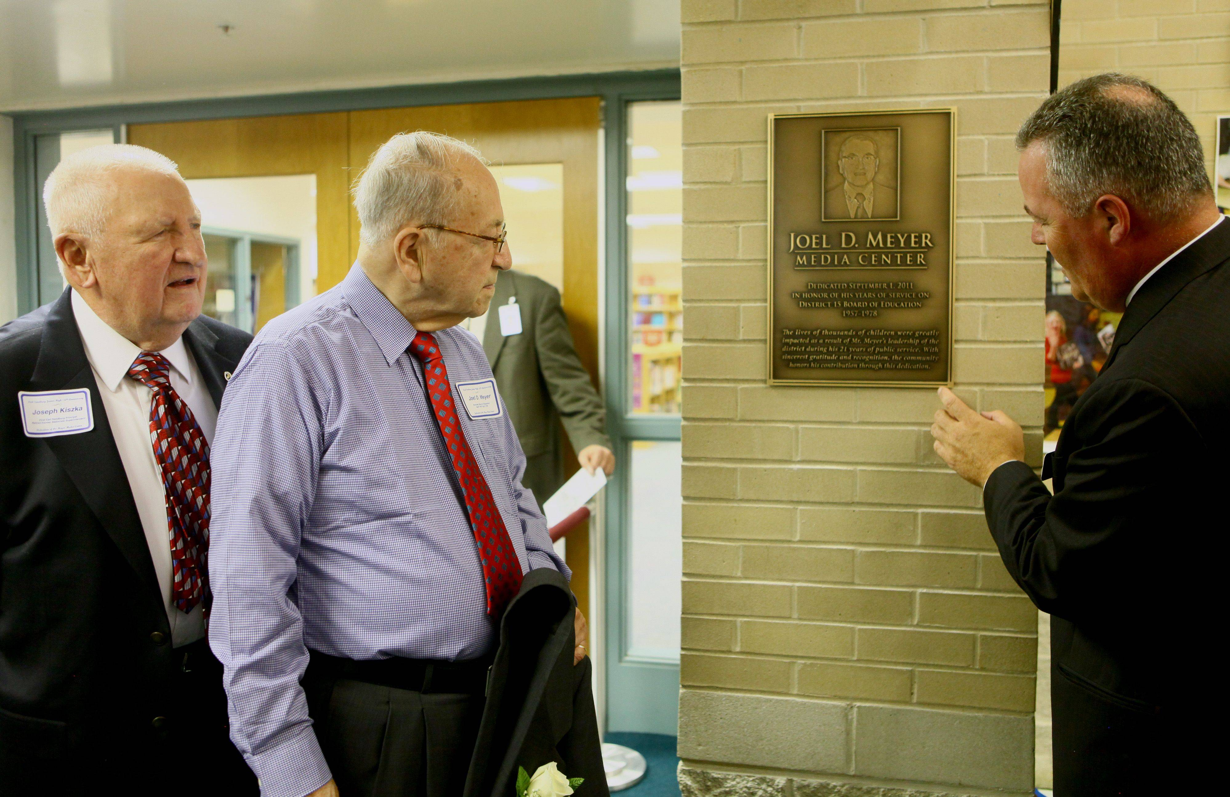 Palatine Township Elementary District 15 Superintendent Scott Thompson, right, shows Joel Meyer and Joseph Kiszka, far left, Carl Sandburg Junior High�s first principal, the plaque in front on the new media center dedicated to Meyer.