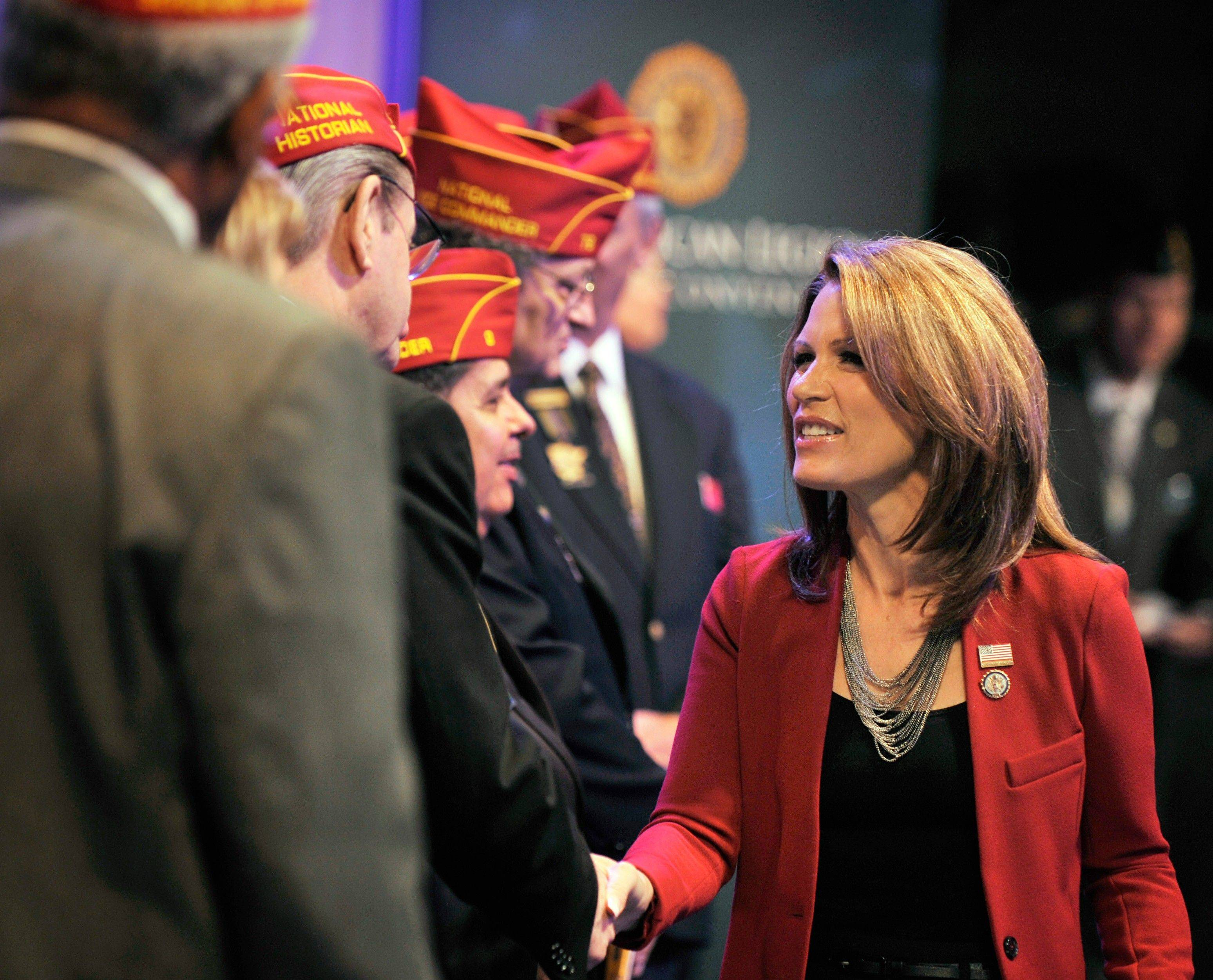 Republican presidential candidate Michele Bachmann greets American Legion officers on stage Thursday after addressing the national convention in Minneapolis.