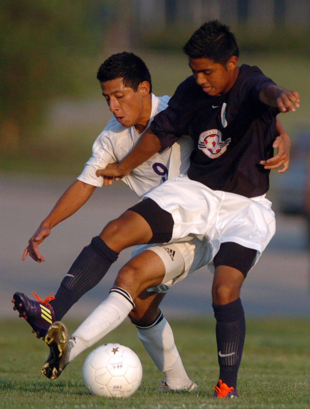 Ismael Morales of Hampshire, left, tries to steal the ball from Alberto Bustamante of South Elgin during action at Hampshire Thursday night.