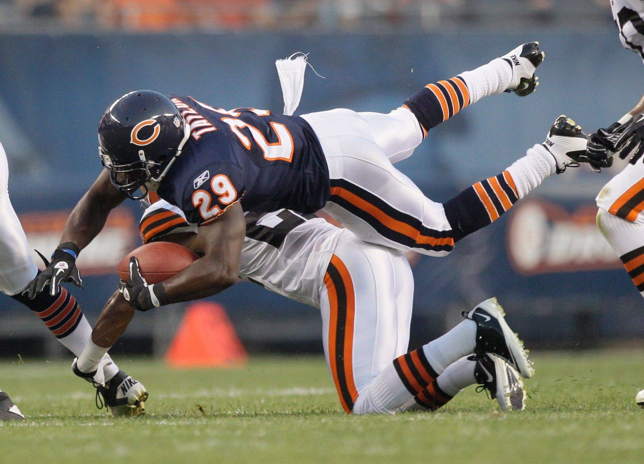Chicago Bears running back Chester Taylor is tackled by Cleveland Browns defensive back Buster Skrine in the first half.