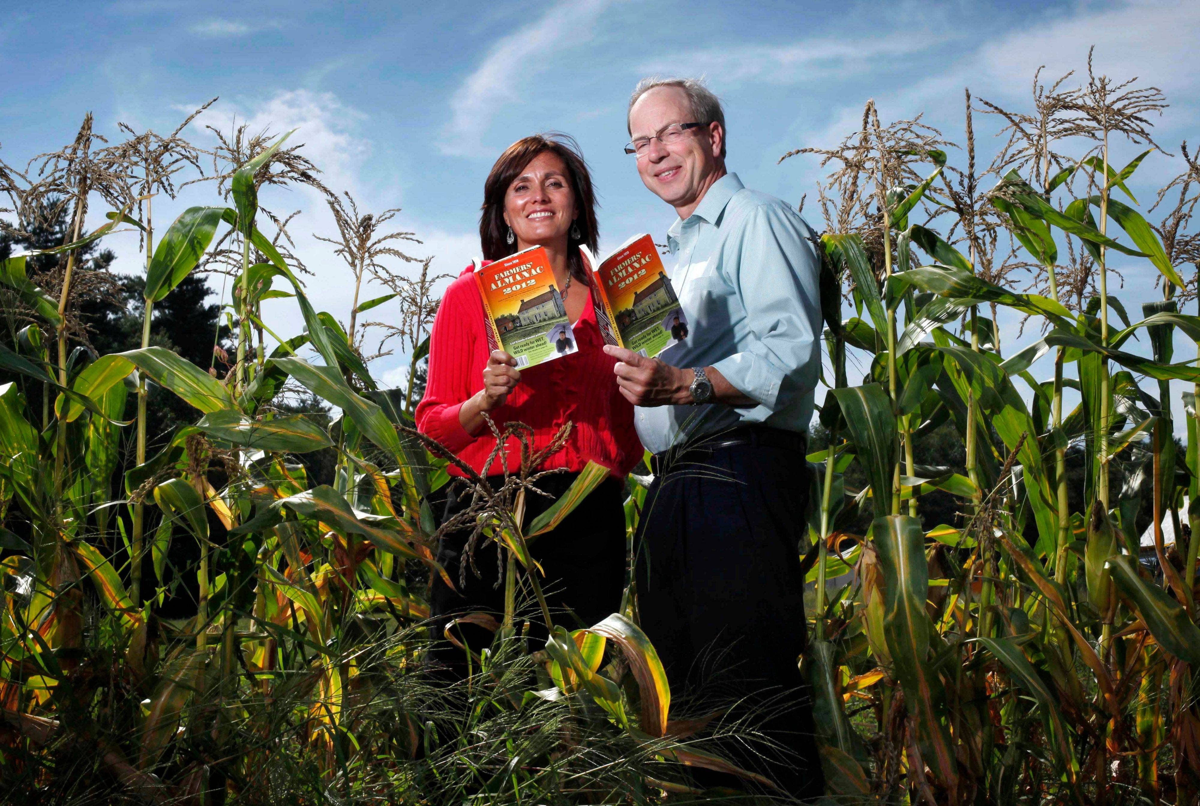 Farmers' Almanac editor Sondra Duncan and publisher Peter Geiger pose in a corn field with the 2012 edition of the almanac. The Almanac is reaching out to readers with an e-reader, mobile website for smart phones, and an app that's in the works.