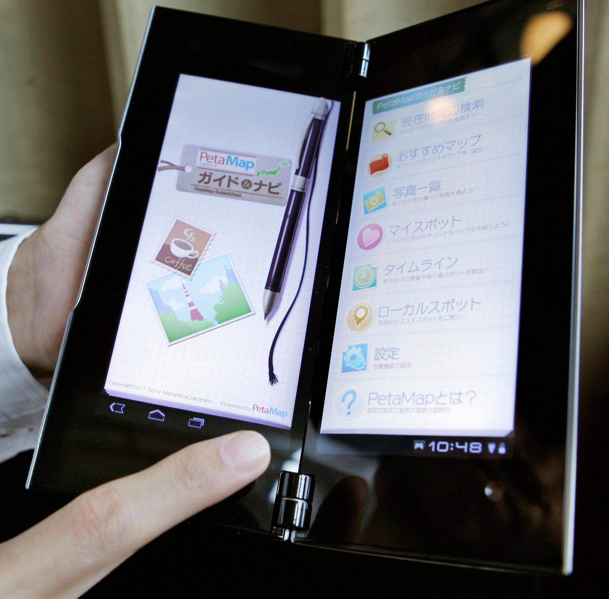 A man demonstrates Sony's new tablet computer Tablet P during a launch event in Tokyo, Thursday. The Tablet P opens like a book to reveal two screens.