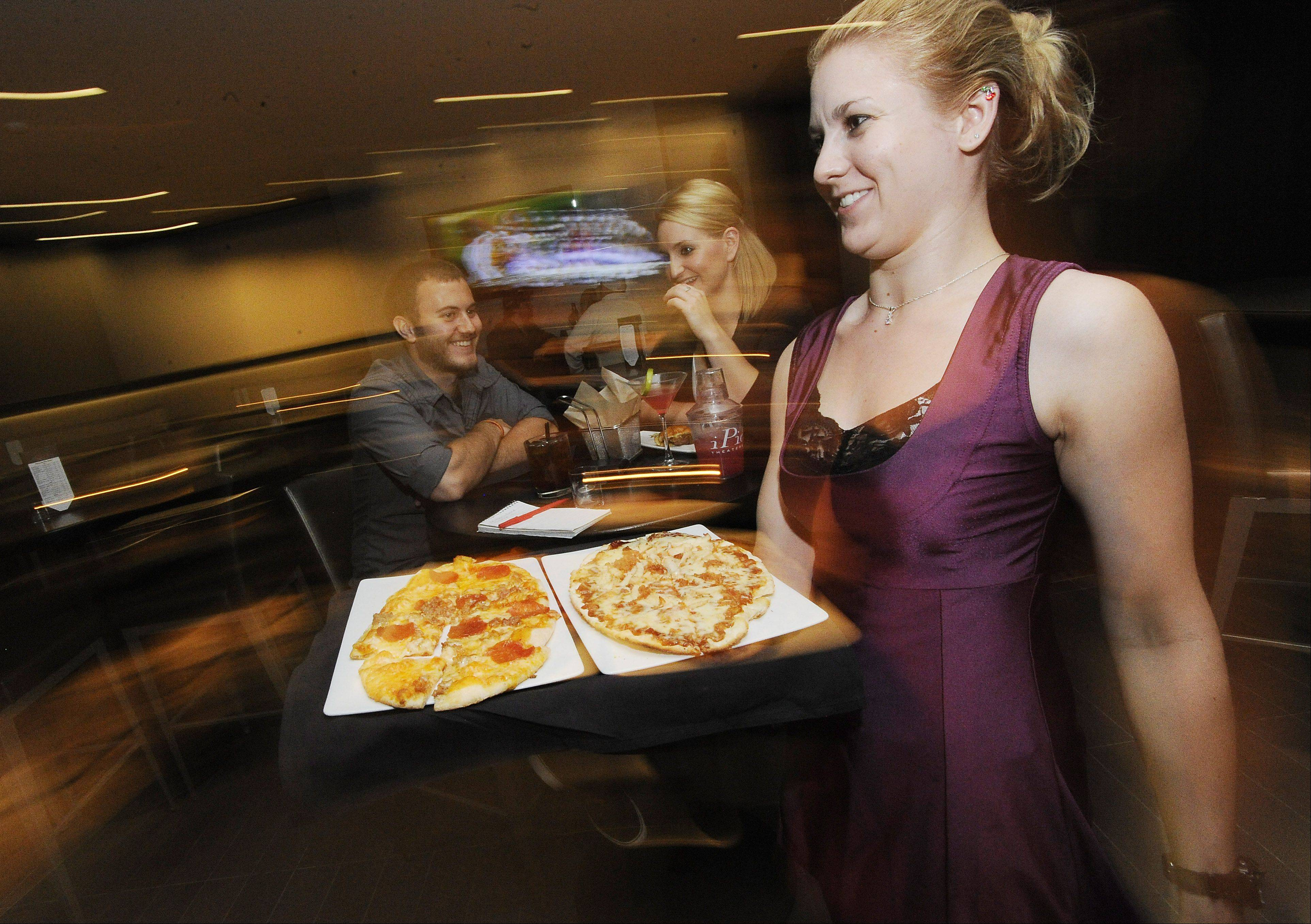 Waitress Tina Krentz of Arlington Heights delivers pizza to patrons as Ryan Mallegri, 23, of Huntley, and Ashley Venturella, 24 of Mount Prospect, enjoy drinks.