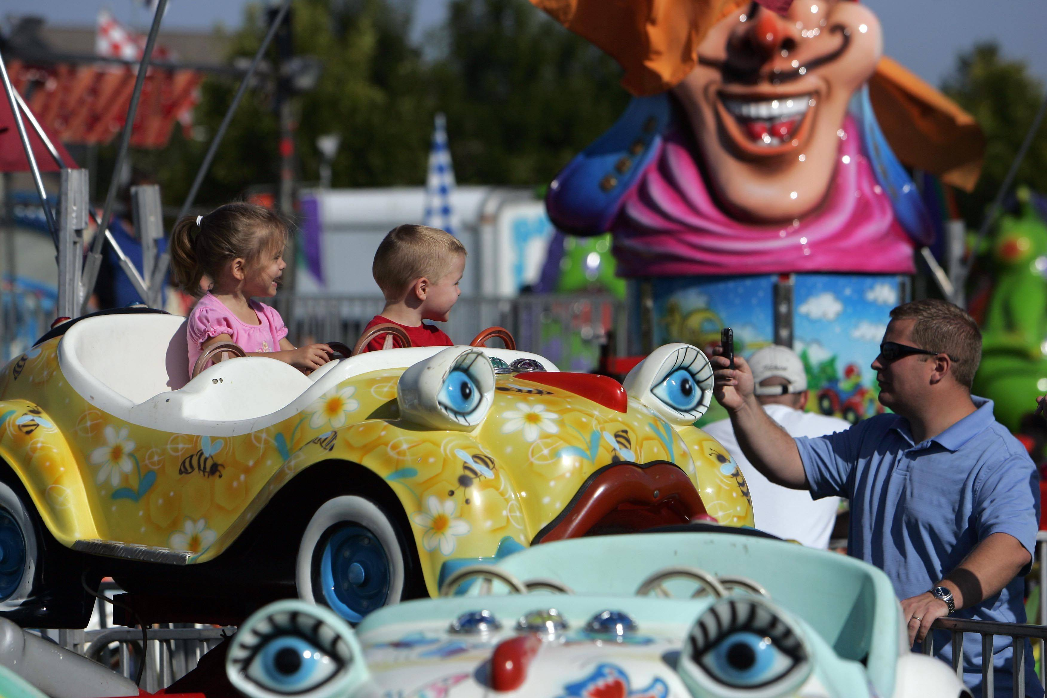 Jason Henning of Lake in the Hills takes a picture of his twins, Ashley, and Brady, both 3, at a previous Summer Sunset Festival in Lake in the Hills.