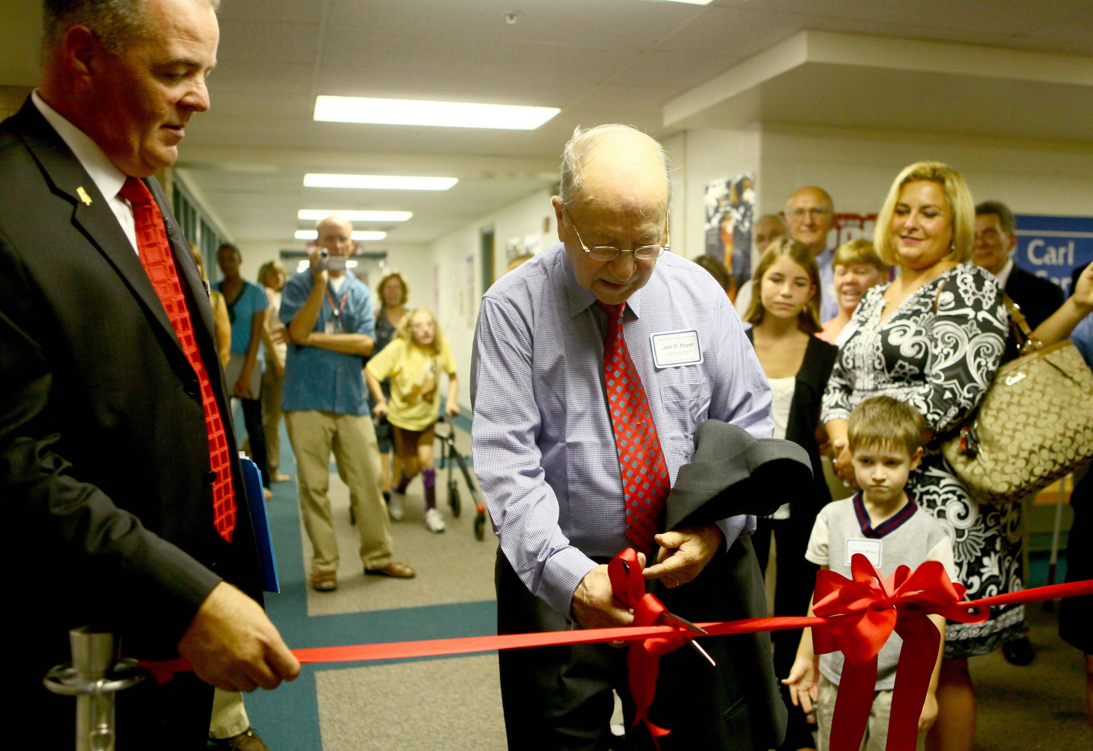 Scott Thompson, Palatine Township Elementary District 15 superintendent, helps Joel Meyer cut the ribbon to officially open the new media center named in his honor at Carl Sandburg Junior High in Rolling Meadows.