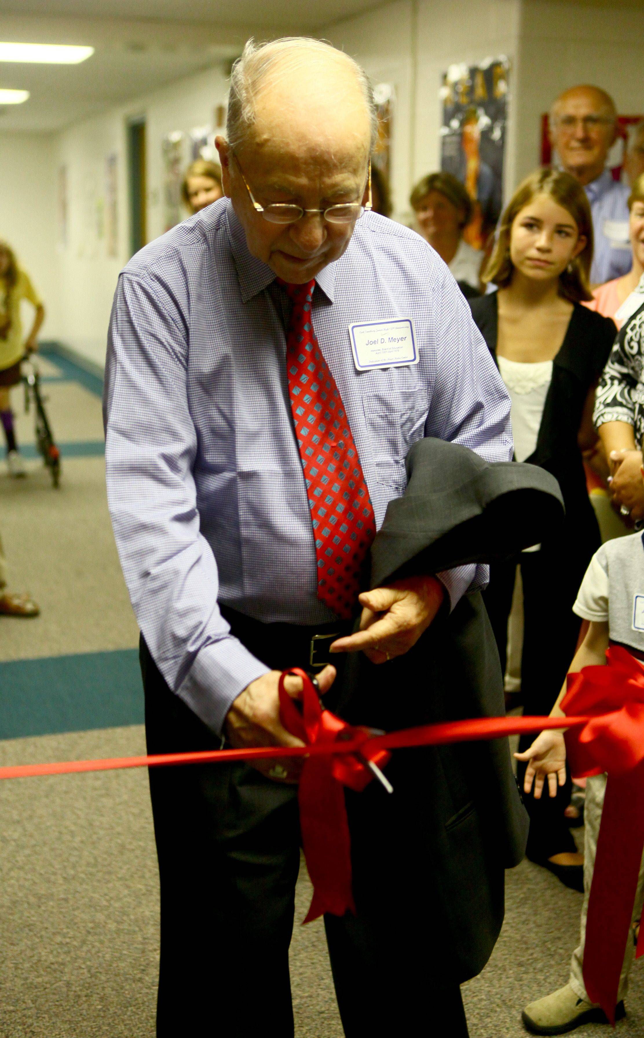 Joel Meyer cuts the ribbon to open the renamed media center at Carl Sandburg Junior High in Rolling Meadows.