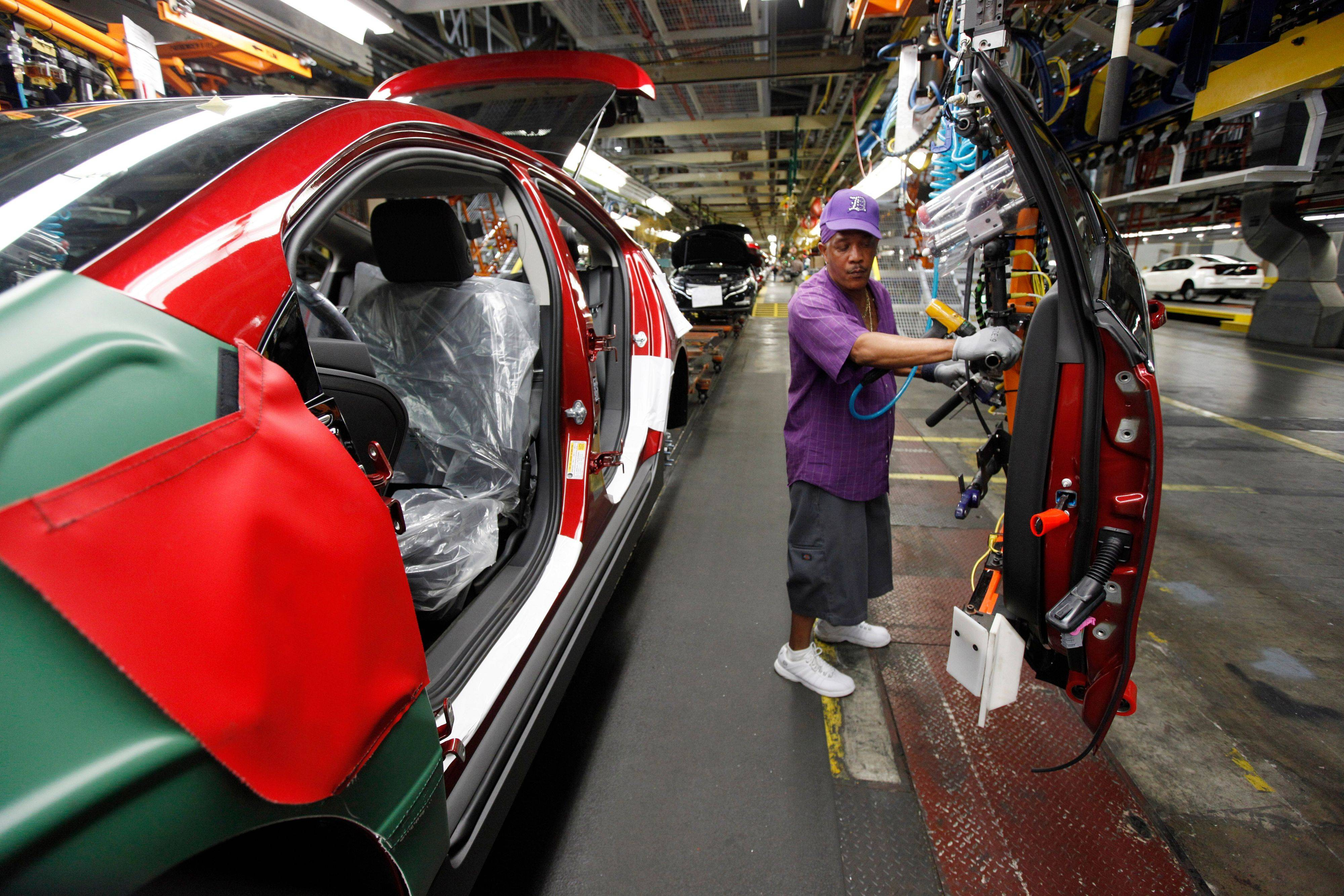 Assembly line worker Edward Houie moves a door into position for a Chevrolet Volt at the General Motors Hamtramck Assembly plant in Hamtramck, Mich. Factory orders rose in July, helped by increased demand for autos and commercial aircraft.