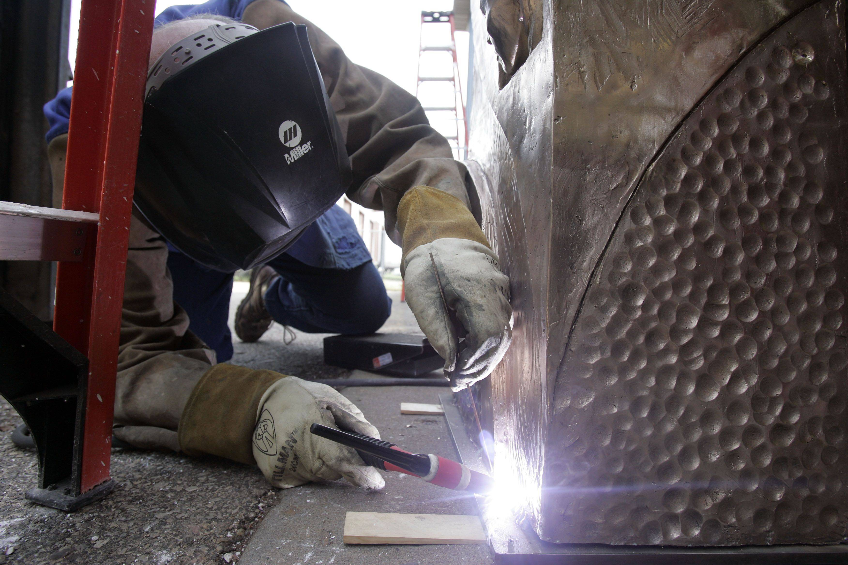 Artist Erik Blome welds the sculpture to the base. Blome did the work -- normally a 1� year project -- in six months.