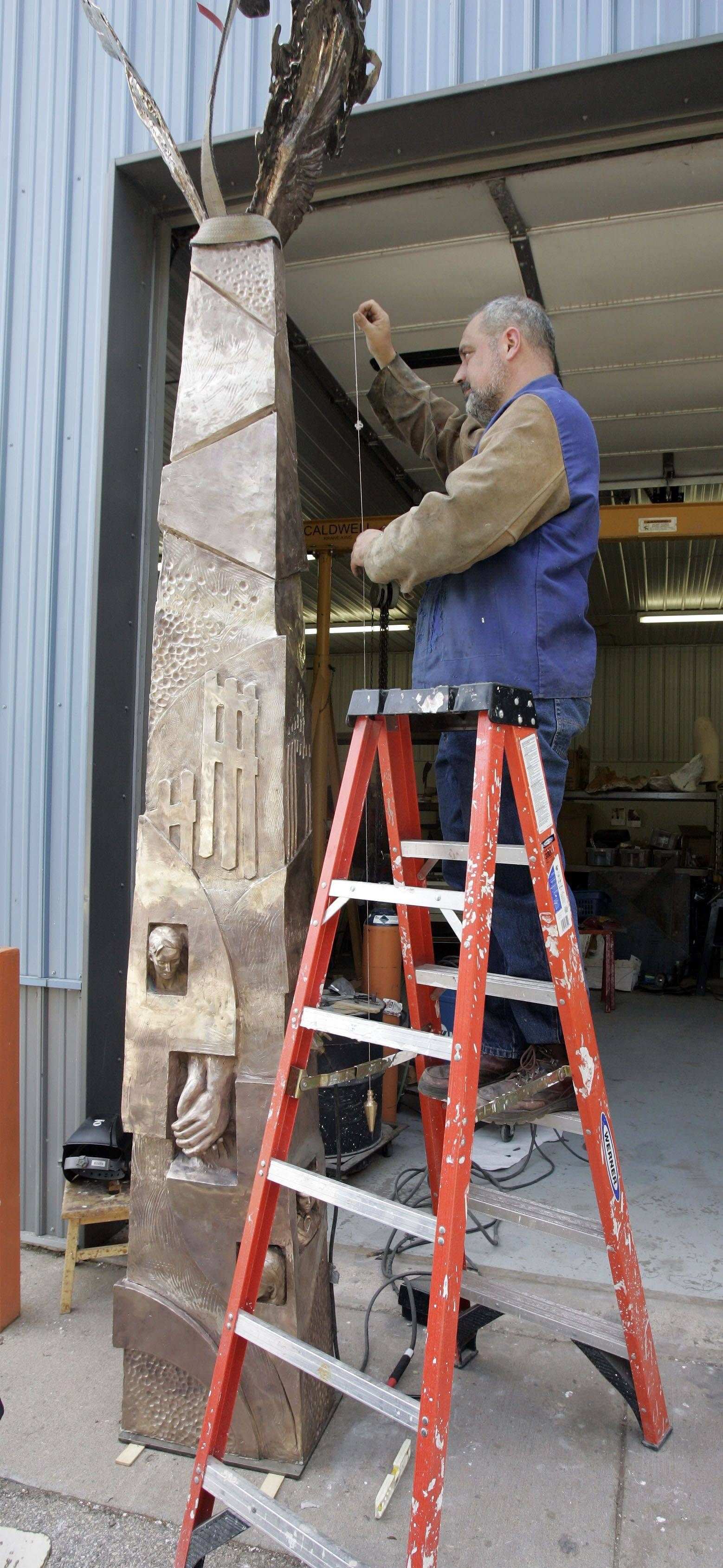Erik Blome checks to make sure that one of the pieces of his sculpture commemorating 9/11 is standing correctly.